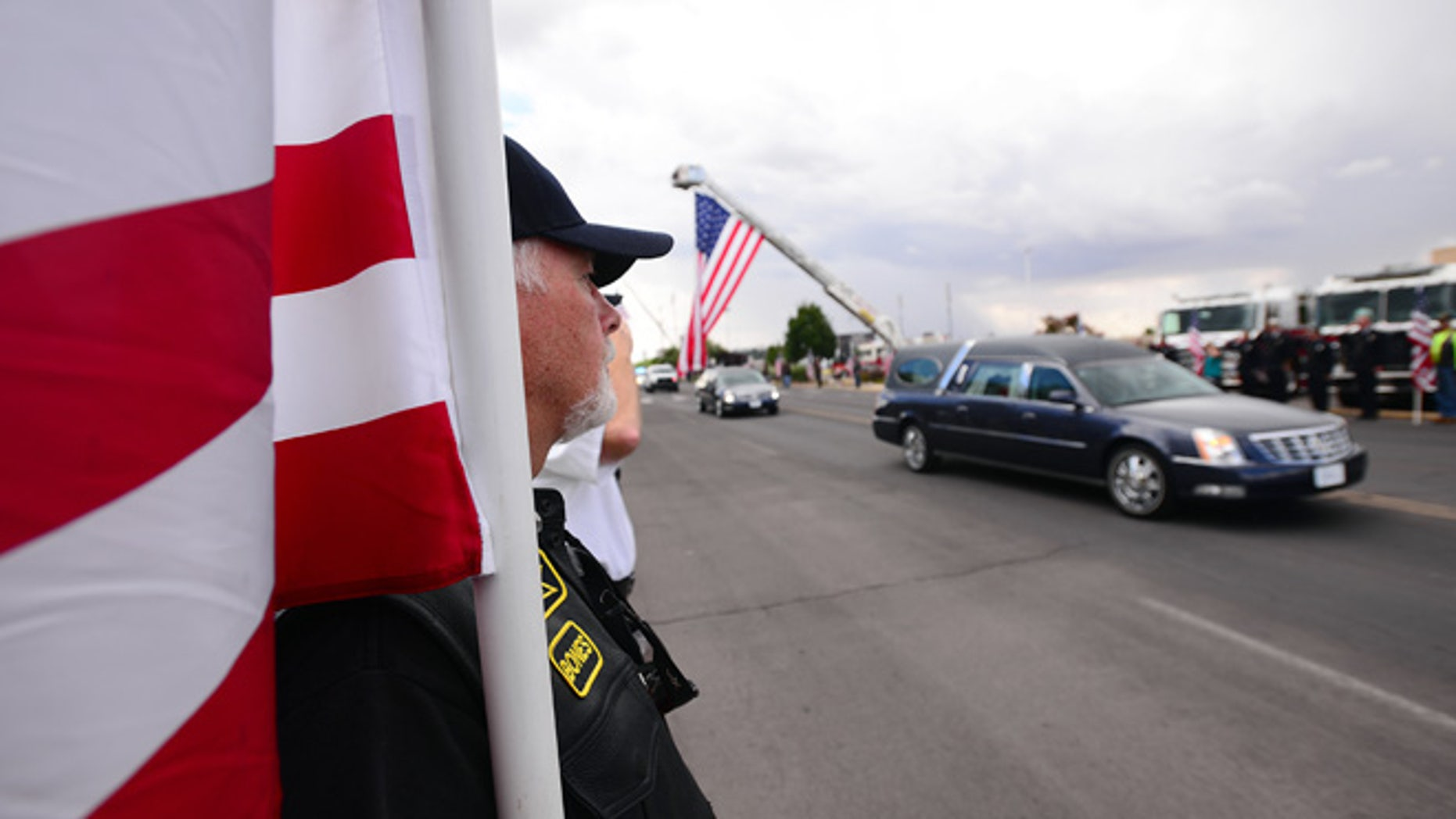 Vietnam War Veteran John Pummell carries a flag while the hearse carrying Hatch Police Officer Jose Chavez approaches the Pan American Center for a public funeral in Las Cruces, N.M., Sunday, Aug. 21, 2016.