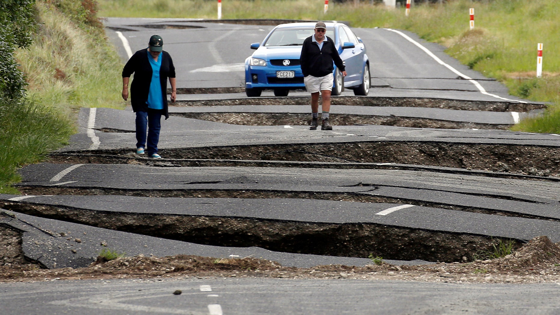 Local residents Chris and Viv Young look at damage caused by an earthquake, along State Highway One near the town of Ward, south of Blenheim on New Zealand's South Island, November 14, 2016. (REUTERS/Anthony Phelps)