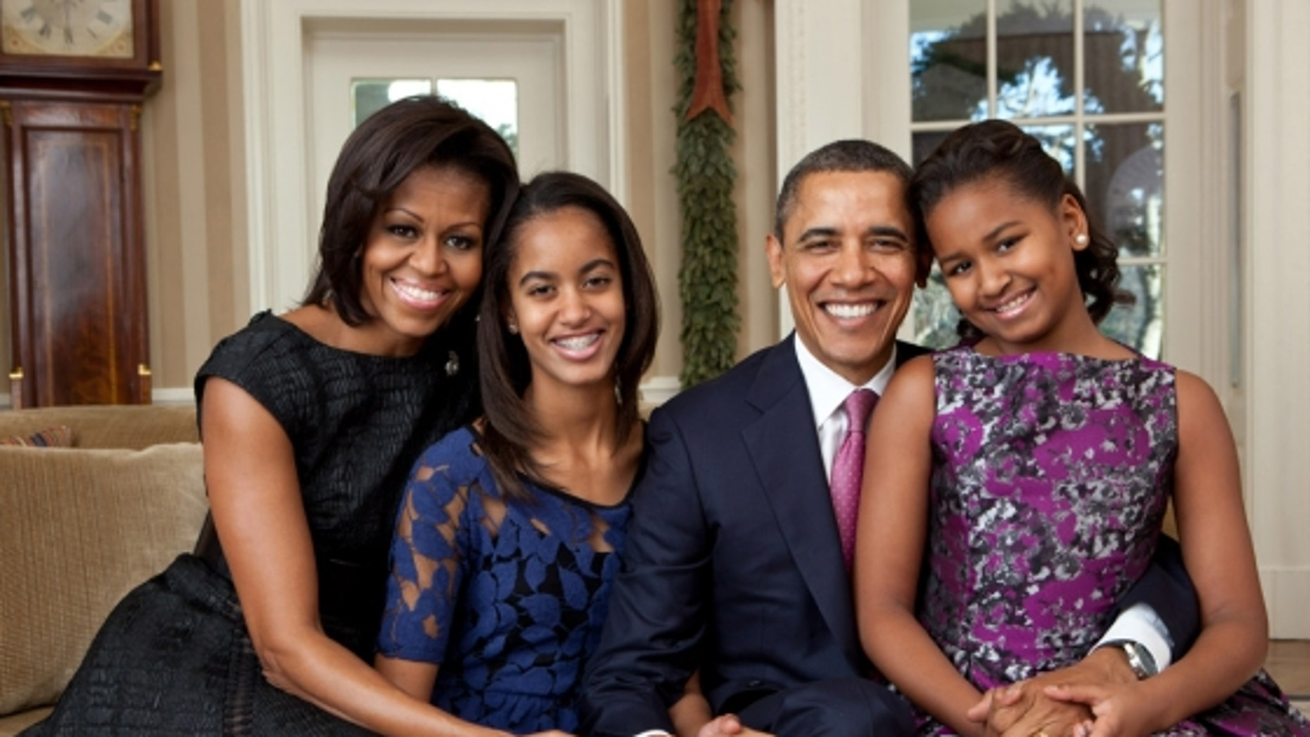 President Barack Obama, First Lady Michelle Obama, and their daughters, Malia, left, and Sasha, right, sit for a family portrait in the Oval Office, Dec. 11, 2011. (Official White House Photo by Pete Souza)