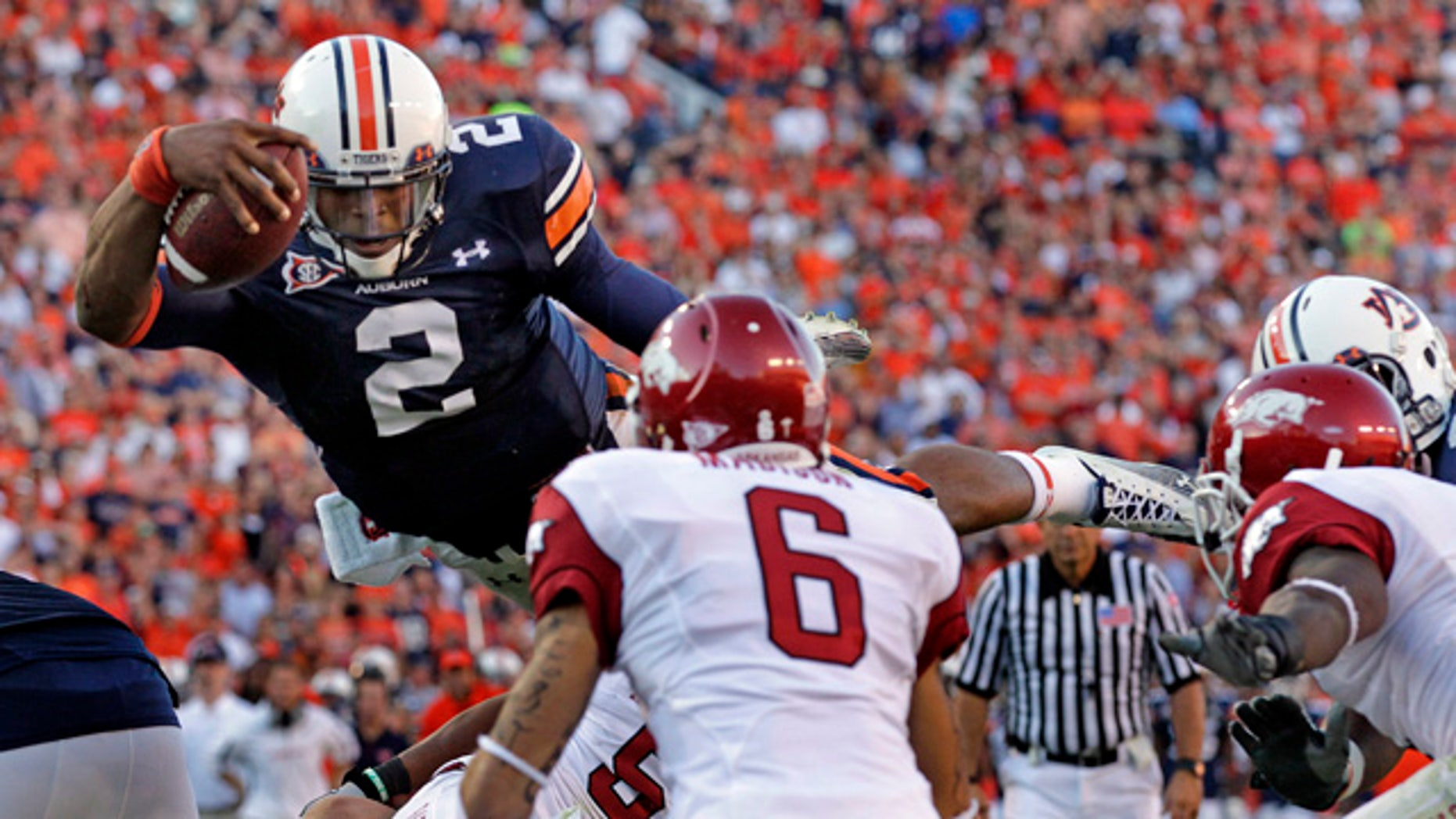 Oct. 16: Auburn quarterback Cameron Newton (2) diving in on for a one-yard touchdown run as Arkansas' Isaac Madison (6) defends during the second half of an NCAA college football game in Auburn, Ala. The Heisman Trophy-winner added AP Player of the Year to his collection of honor on Dec. 22. (AP)