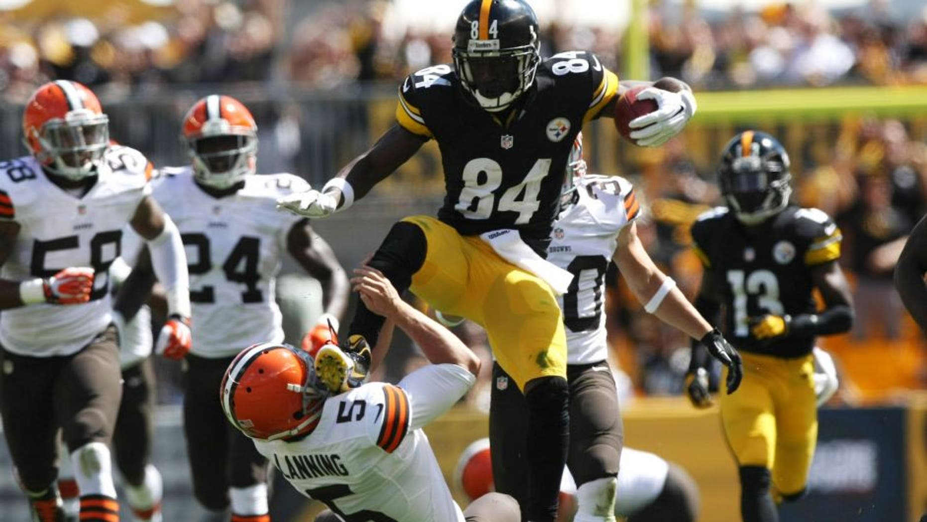 Sep 7, 2014; Pittsburgh, PA, USA; Pittsburgh Steelers wide receiver Antonio Brown (84) runs over Cleveland Browns punter Spencer Lanning (5) during the first half at Heinz Field. Brown was flagged on the play. Mandatory Credit: Jason Bridge-USA TODAY Sports