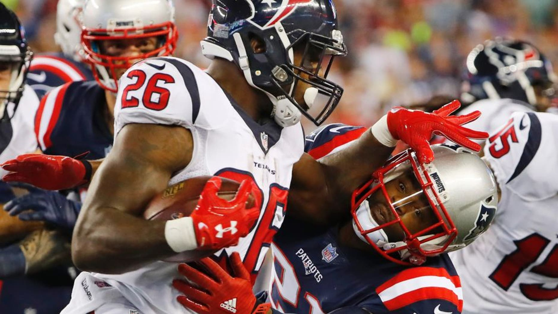 Sep 22, 2016; Foxborough, MA, USA; Houston Texans running back Lamar Miller (26) tries to push away New England Patriots cornerback Malcolm Butler (21) during the first half at Gillette Stadium. Mandatory Credit: Winslow Townson-USA TODAY Sports