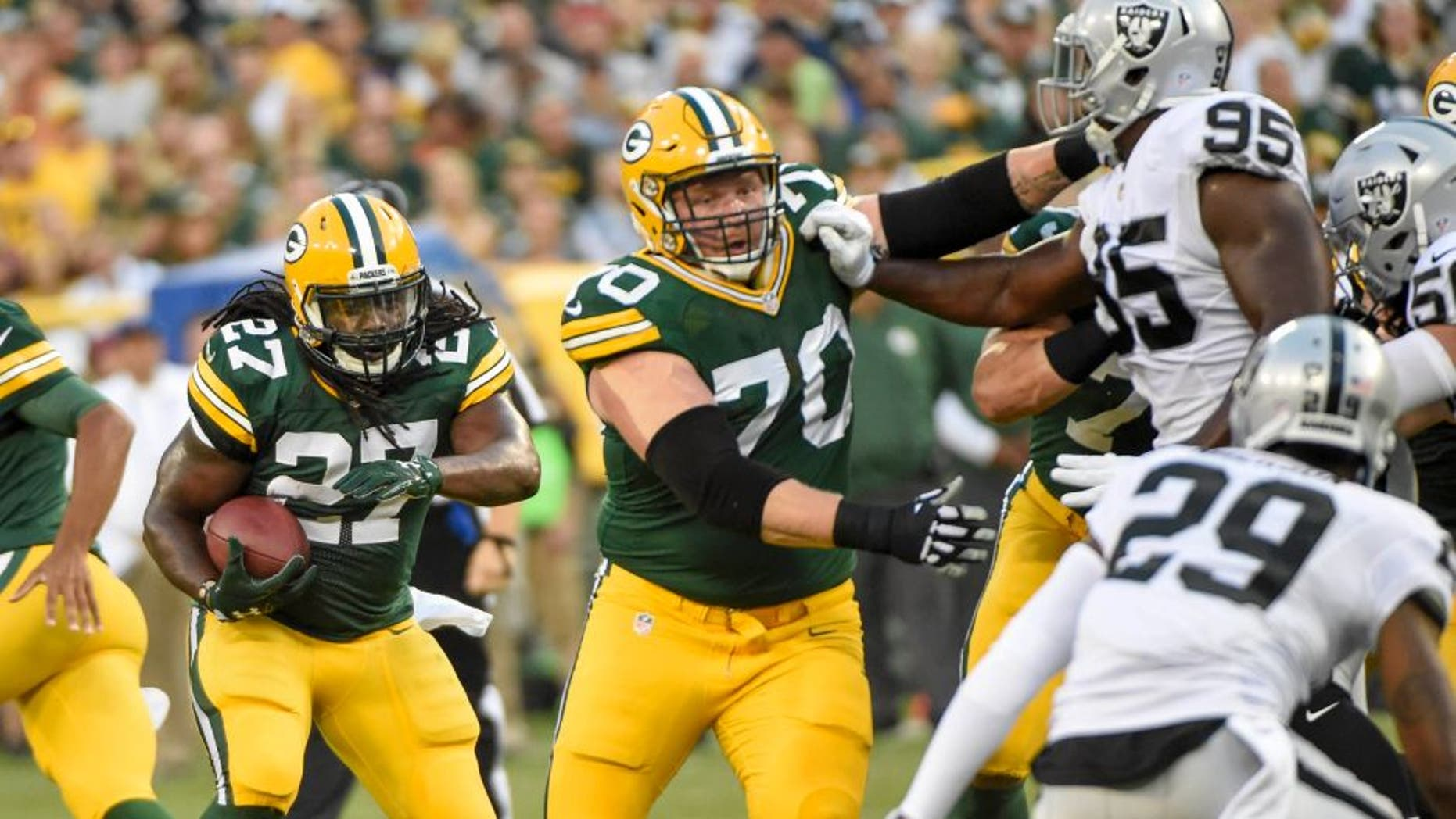 Aug 18, 2016; Green Bay, WI, USA; Green Bay Packers running back Eddie Lacy (27) follows a block by guard T.J. Lang (70) in the first quarter during the game against the Oakland Raiders at Lambeau Field. Mandatory Credit: Benny Sieu-USA TODAY Sports