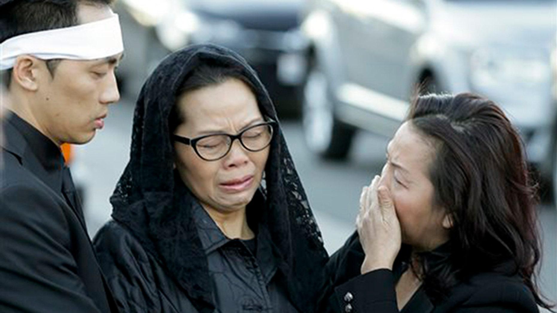 Van Thanh Nguyen, center, arrives for her daughter Tin Nguyen's funeral on Saturday, Dec. 12, 2015 in Santa Ana, Calif. Nguyen died in the mass shootings in San Bernardino, Calif., on Dec. 2. (AP Photo/Chris Carlson)