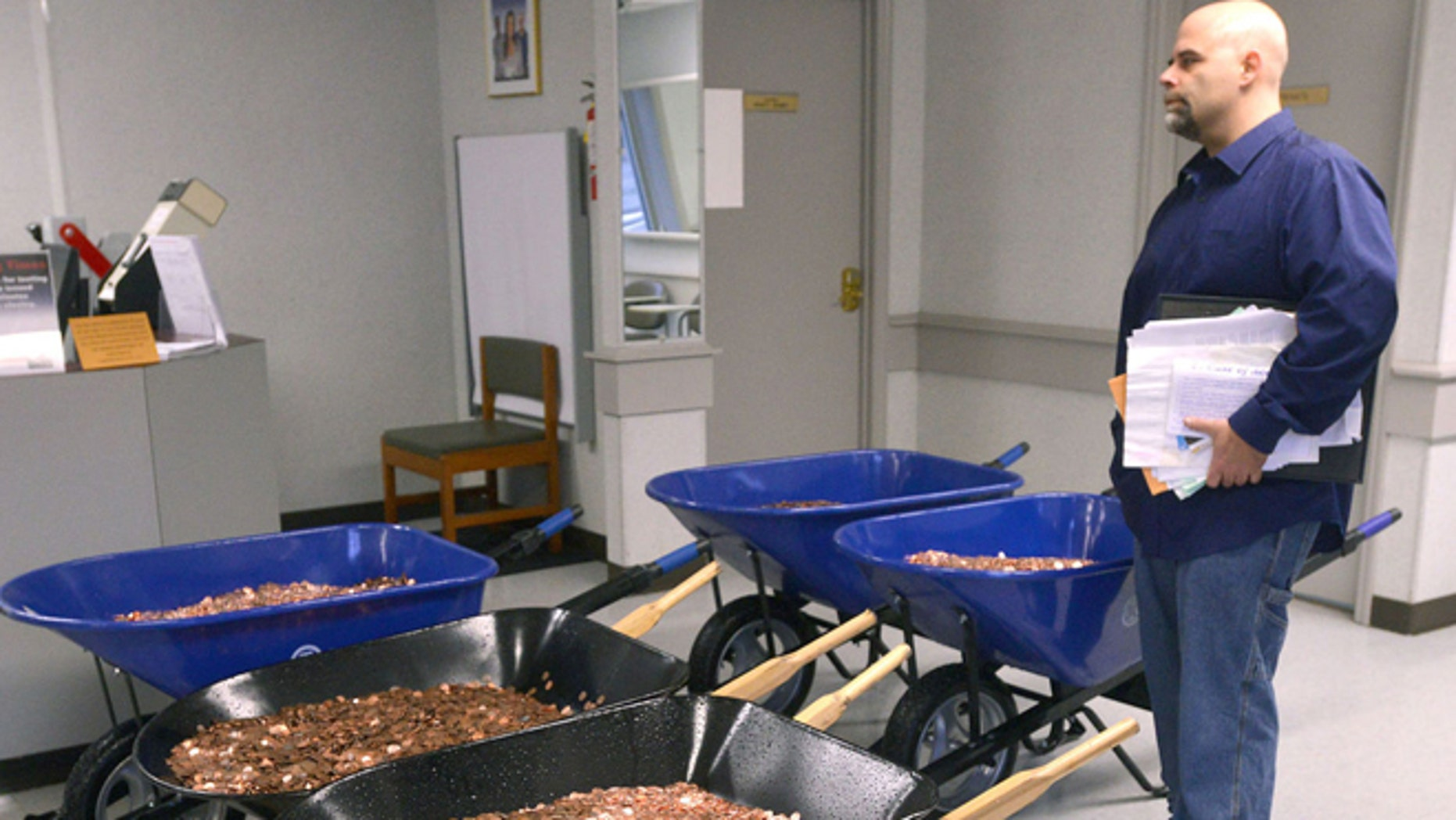Nick Stafford waits on line at local DMV with five wheelbarrows full of pennies. (David Crigger/Bristol Herald Courier)