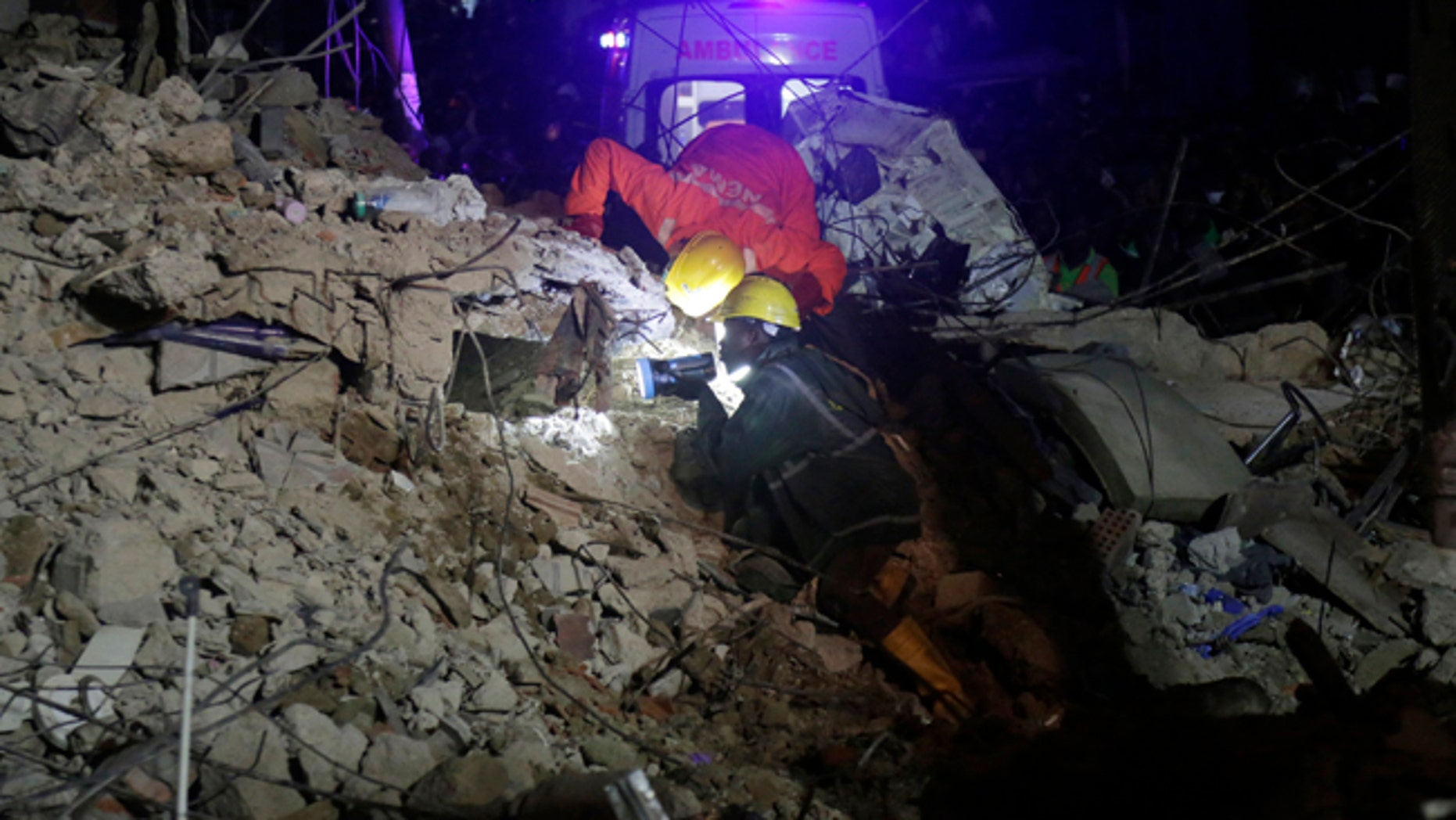 Rescue workers use flashlights to search for survivors at the rubbles of a collapsed building in a densely populated neighborhood in Lagos, Nigeria. Tuesday, July 25, 2017. Rescue work is still ongoing. (AP Photo/Sunday Alamba)