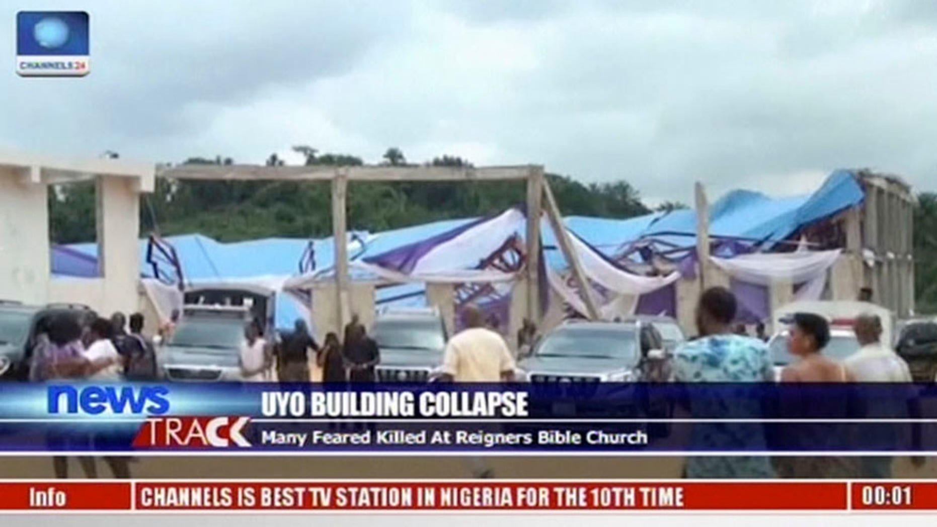 In this image taken from video people stand at the scene after the roof of The Reigners Bible Church International collapsed onto worshippers in Uyo, southern Nigeria on Saturday, Dec. 10, 2016, killing dozens, witnesses and an official said. (Channels TV via AP)