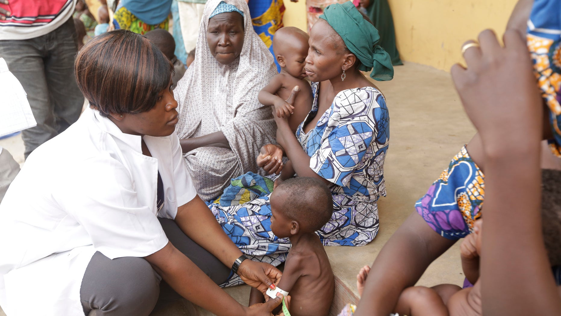 In this Sunday , May. 3, 2015 file photo a doctor attends to a Malnourished child as women and children rescued by Nigerian soldiers wait to receive treatment at a refugee camp in Yola, Nigeria.