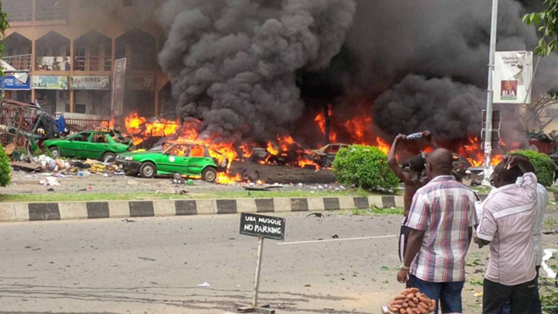 June 25, 2014: People watch as smoke fills the sky, after an explosion, at a shopping mall in Abuja, Nigeria. An explosion rocked a shopping mall in Nigeria's capital, Abuja, on Wednesday and police say at least over 20 people have been killed and many wounded.