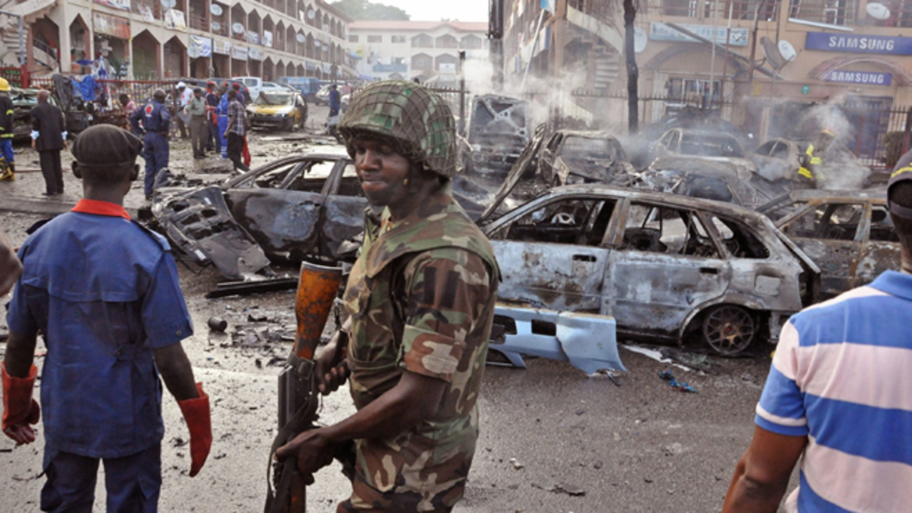 June, 25, 2014: In this file photo, a Nigerian soldier, center, walks, at the scene of an explosion in Abuja, Nigeria. A car bomb exploded in a market in Nigeria's northeastern city of Maiduguri on Tuesday morning, July 1, 2014  and dozens of people are feared dead, witnesses said.