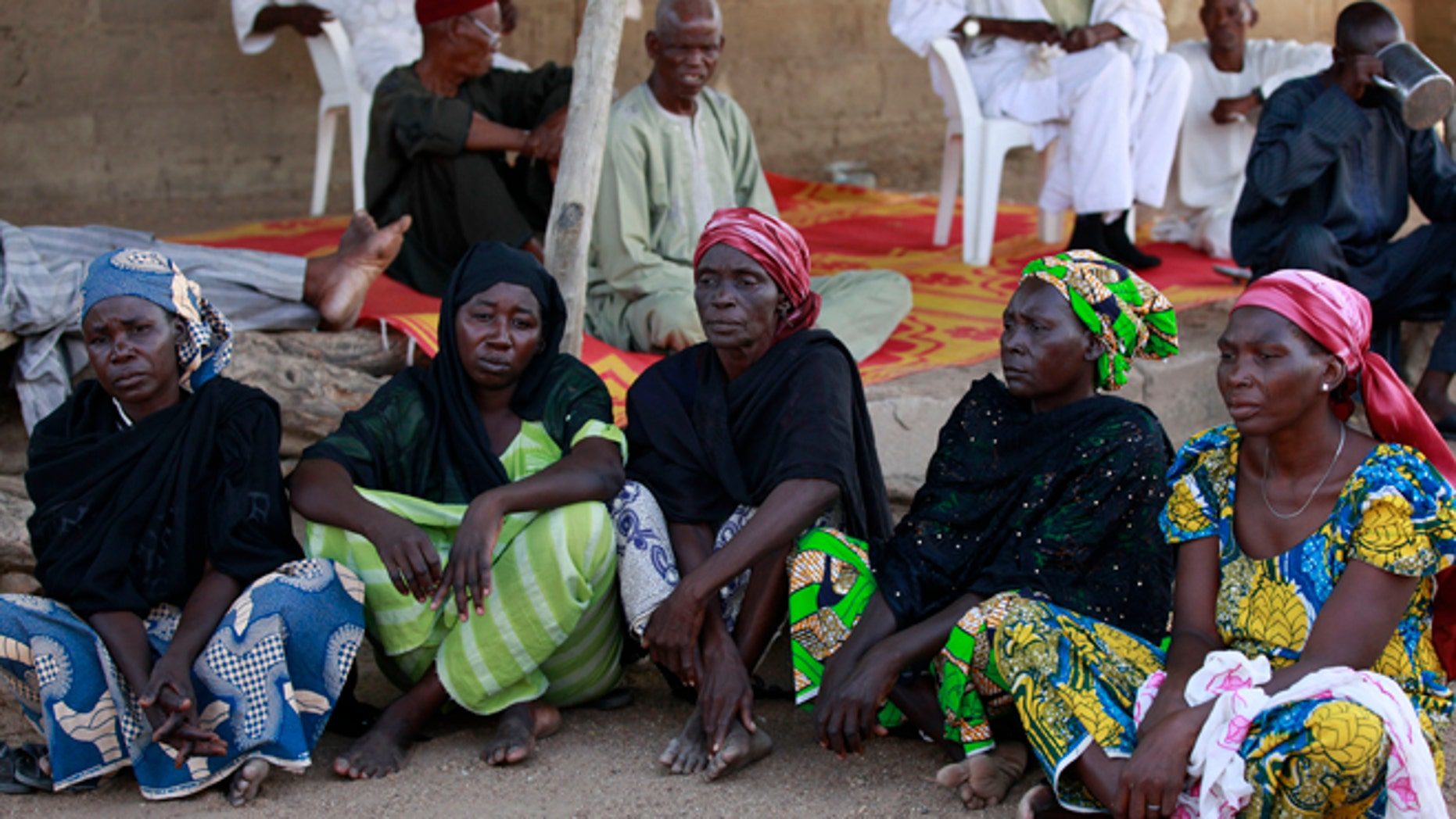 In this Sunday, May 18, 2014 file photo some of the parents of the kidnapped school girls sit outside a compound during a meeting in Chibok, Nigeria. At least 11 parents of the more than 200 kidnapped Nigerian schoolgirls will never see their daughters again. Since the mass abduction of the schoolgirls by Islamic extremists three months ago, at least 11 of their parents have died and their hometown, Chibok, is under siege from the militants, residents report.