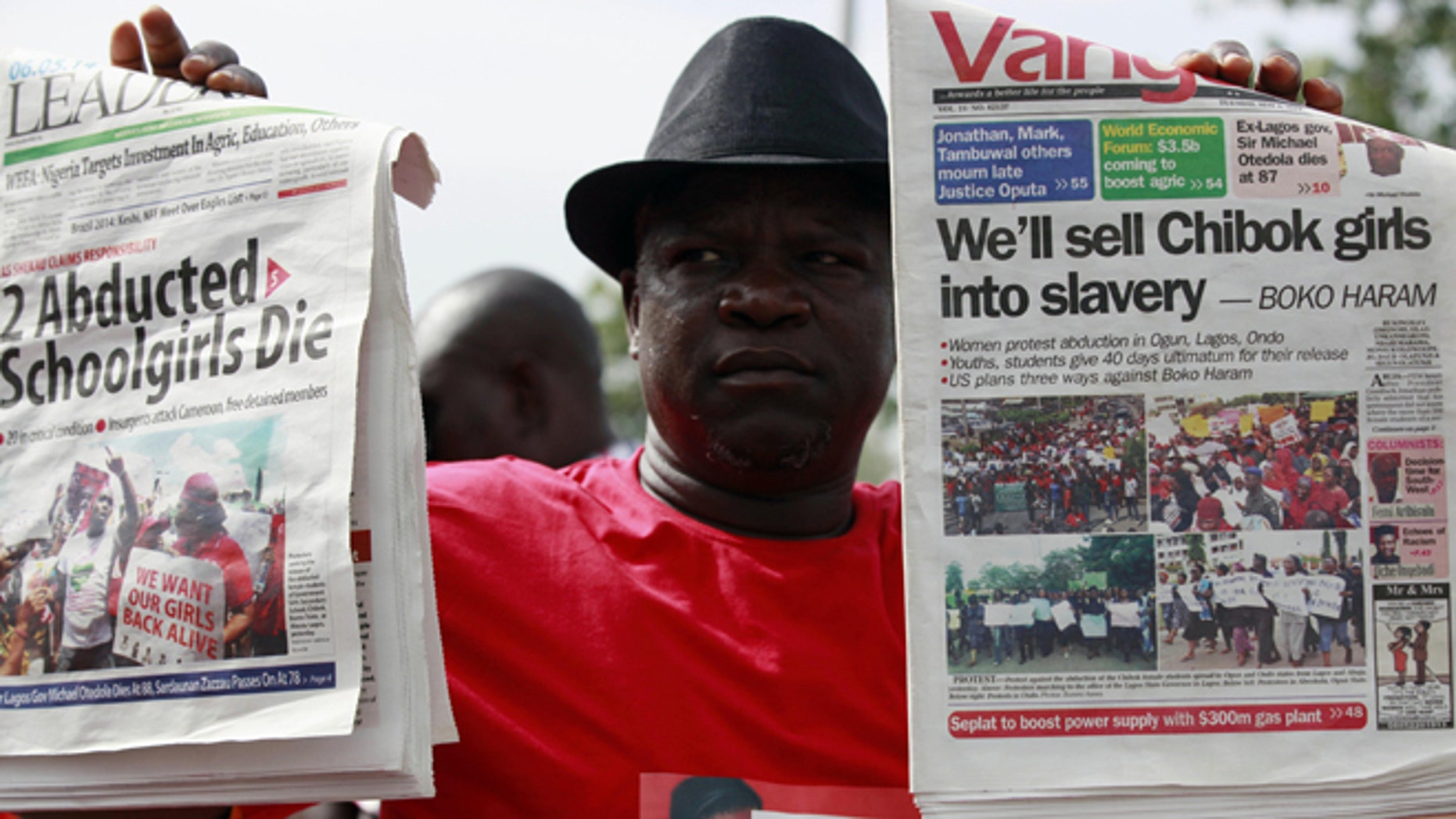 May 6, 2014: A man display copies of local newspapers during a demonstration calling on the government to rescue kidnapped school girls from Chibok government secondary school, outside the defense  headquarters, in Abuja, Nigeria.