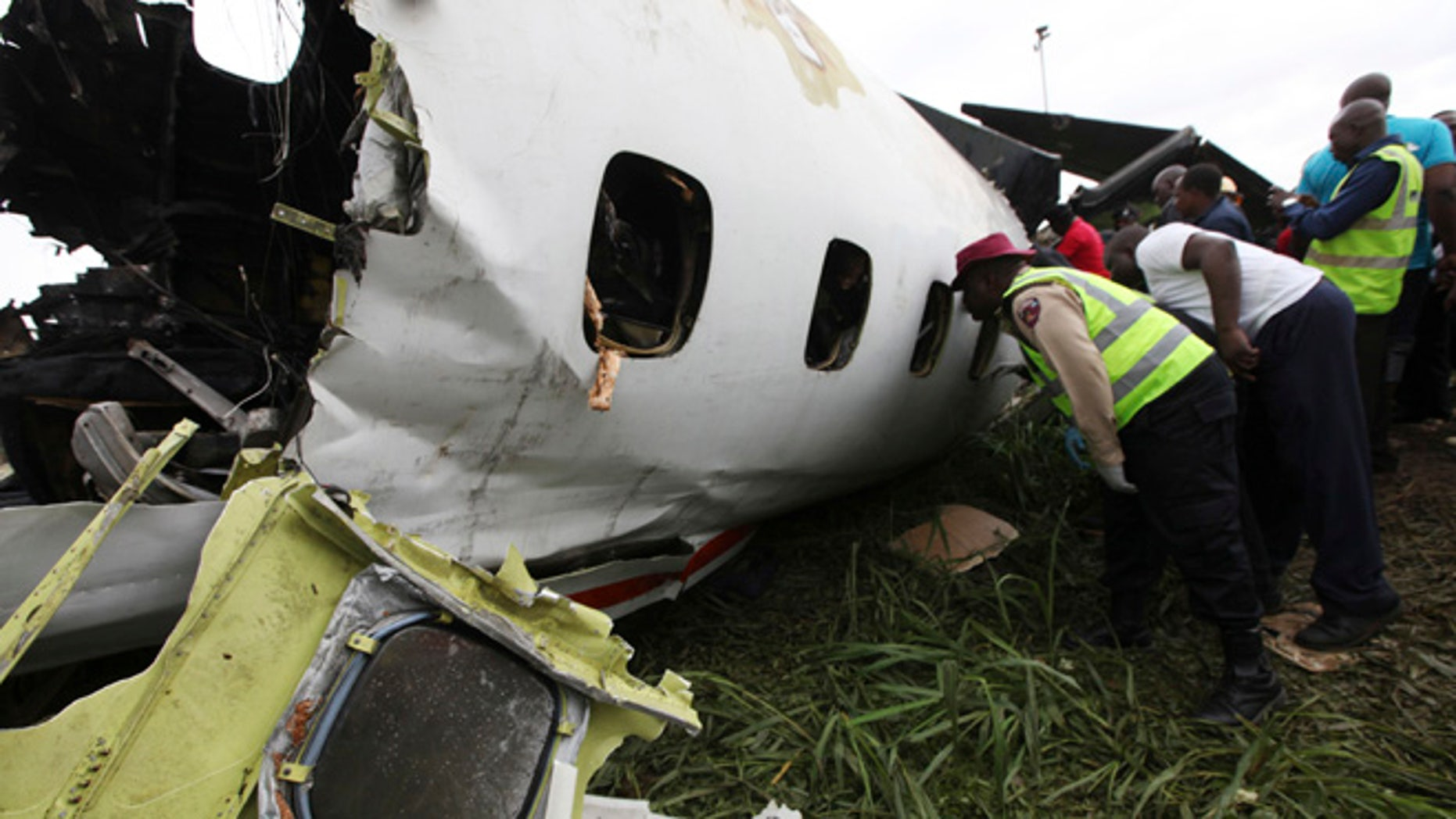 Oct. 3, 2013: Rescue workers peer into the wreckage of a charter passenger jet which crashed soon after take off from Lagos airport, Nigeria. Officials said there were casualties but refused to confirm reports of several deaths.