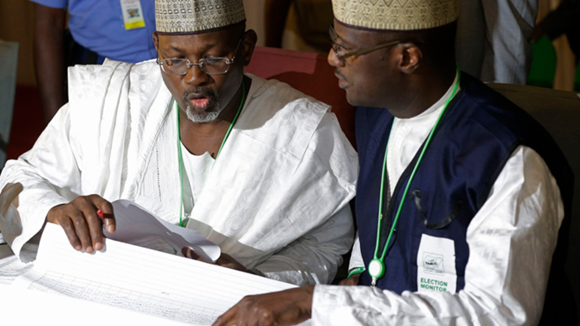 March 30, 2015: Independent National Electoral Commission chairman, Attahiru Jega, left, views election results at the coalition center in Abuja, Nigeria, Monday.