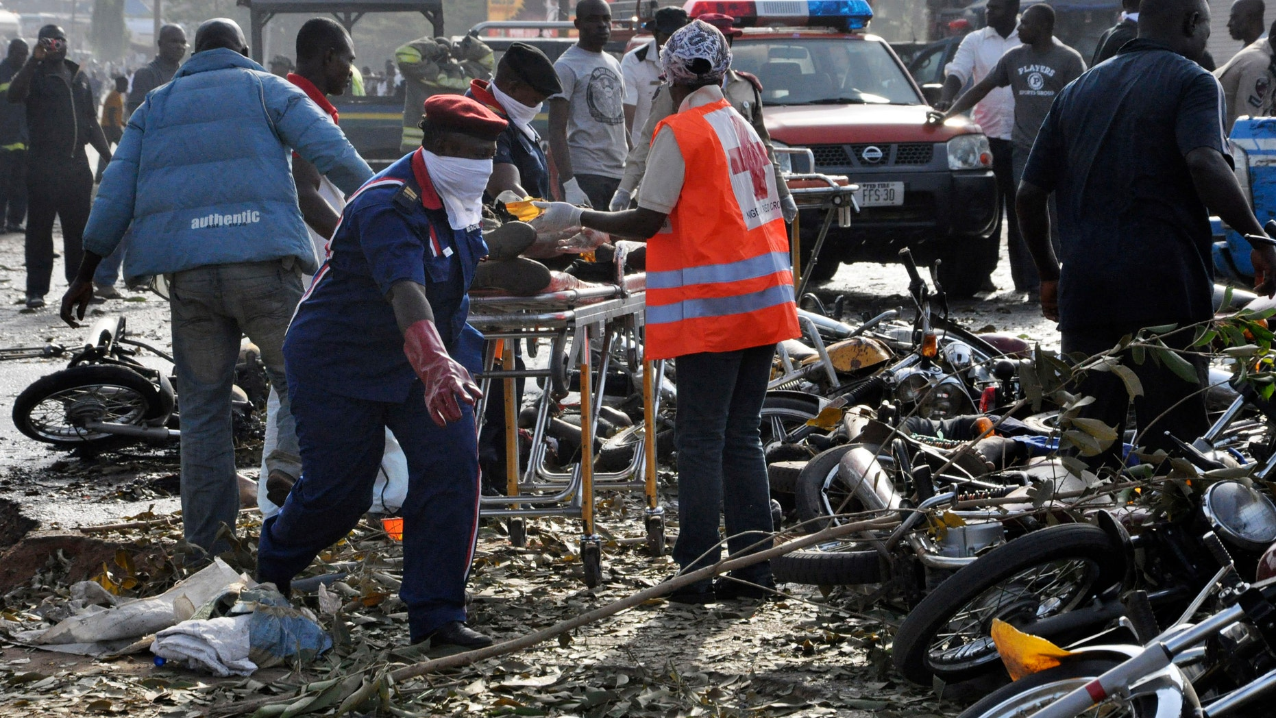 April 14, 2014: Rescue workers work to recover victims at the site of a blast at the Nyanya Motor Park, about 10 miles from the center of Abuja, Nigeria. An explosion blasted through a busy commuter bus station on the outskirts of Abuja as hundreds of people were traveling to work.