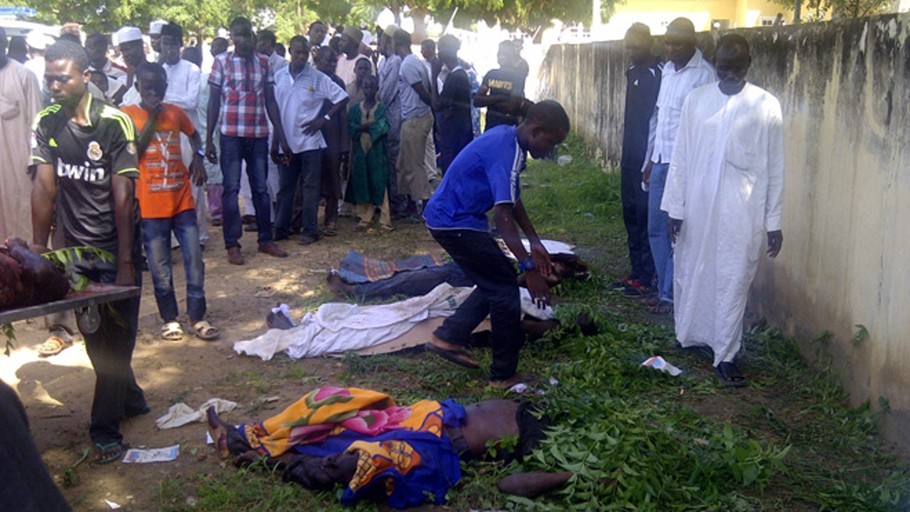 Sept. 29, 2013: In this image taken with a mobile phone, rescue workers and family members gather to identify the shrouded bodies of students killed following an attack by Islamist extremists on an agricultural college in Gujba, Nigeria.