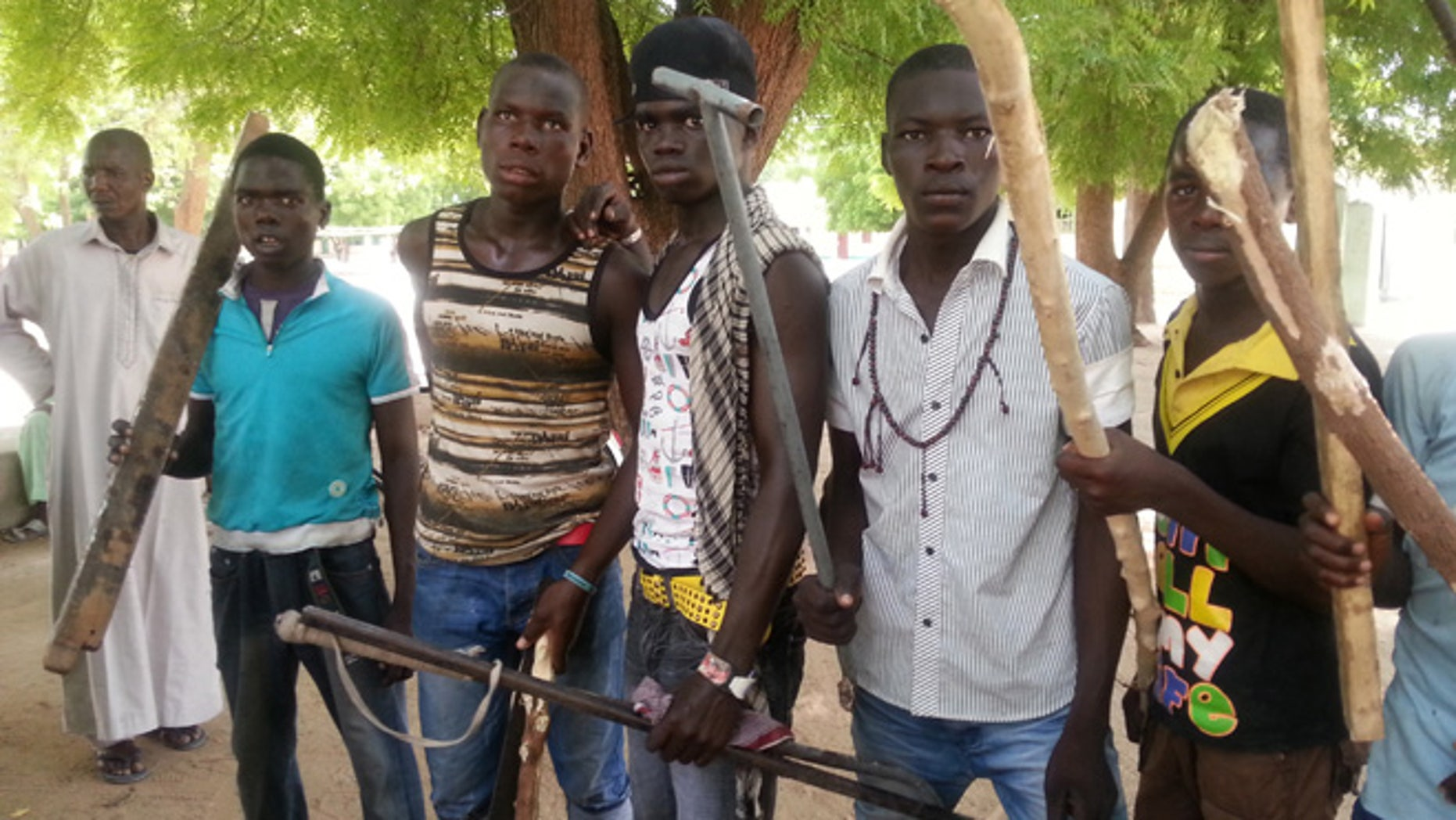June 11, 2013: In this photo taken with a mobile phone, vigilante youths pose for a photographs in Maiduguri, Nigeria. As soldiers continue an offensive against radical Islamic extremists in northeast Nigeria, young men armed with machetes and sticks have now entered the streets of the regions biggest city, targeting suspected fighters. The members of the Civilian JTF, a play off the acronym used to describe the joint military and police taskforce in the region, already have come under attack from extremists for pointing out suspects to soldiers. However, it remains unclear what happens to those the group points out, as some suspects in Maiduguri have already been shot dead by security forces and left rotting in ditches in the city.