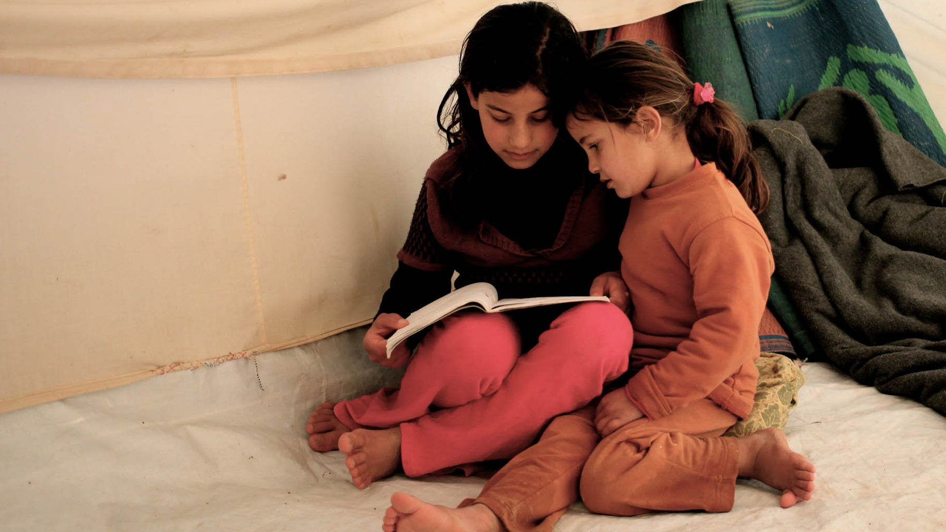Syrian refugee girls, Fatima Teeme, right, and Sara Teeme, from Homs, read a book inside their tent, as their father Ibraheem Teeme speaks to The Associated Press, at Zaatari refugee camp, near the Syrian border in Mafraq, Jordan, Monday, Dec. 16, 2013. NRC began distributing stoves to Syrian refugees at the Zaatari camp in Jordan on Monday, as bitter winter weather made living conditions worse. (AP Photo/Mohammad Hannon)