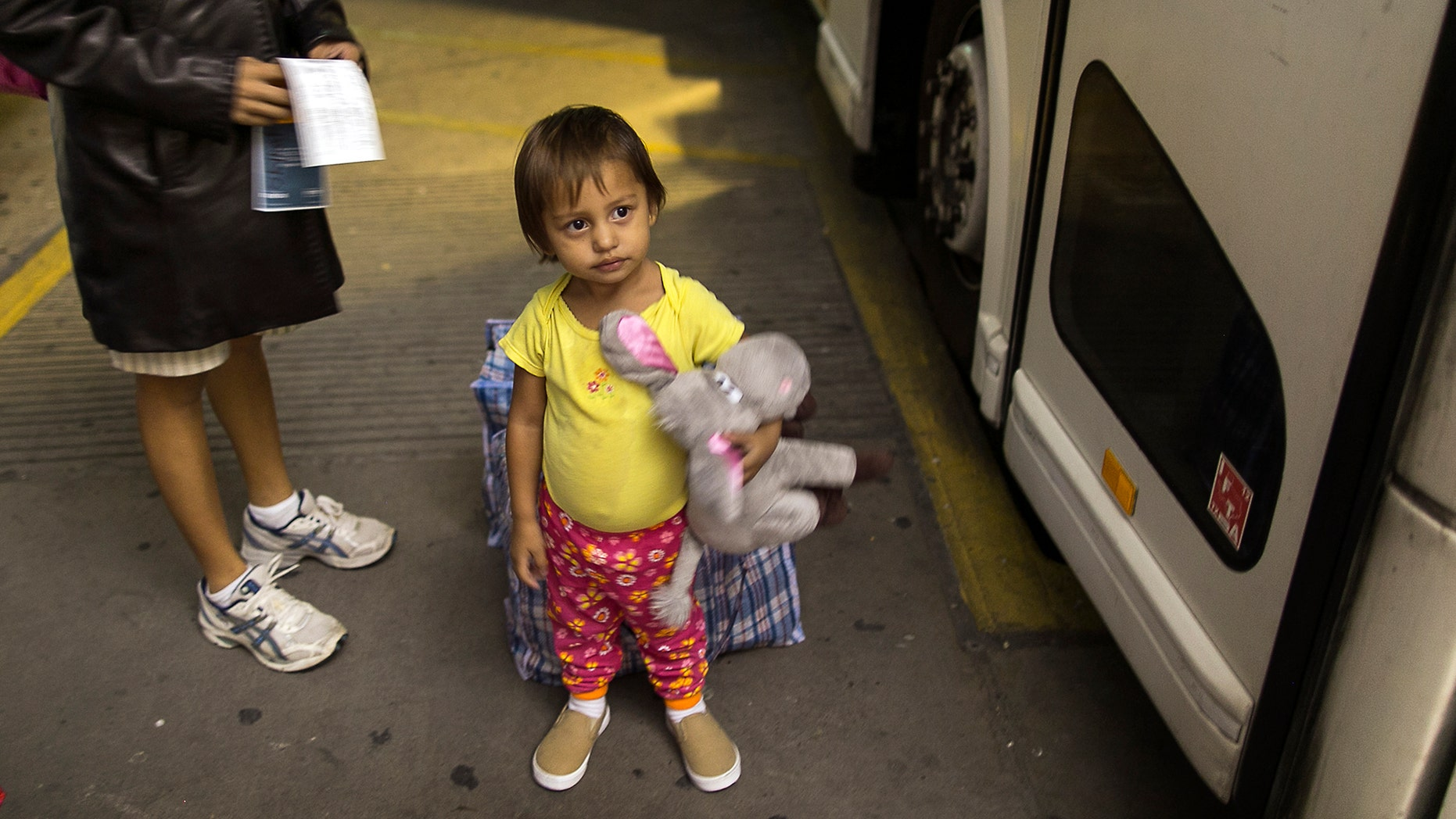 Two-year-old Adriana Ortez and her mother wait to board a bus leaving the city in McAllen, Texas.