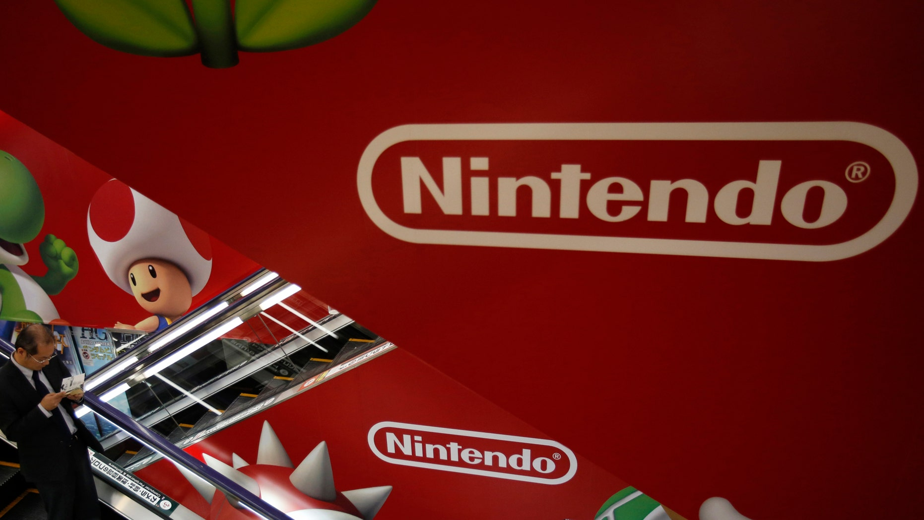 "File photo: A shopper rides the escalator past Nintendo advertisements at an electronics retail store in Tokyo January 20, 2014. Shares in Nintendo Co Ltd tumbled by nearly a fifth on Monday after it warned of a third straight year of operating losses, heaping pressure on the creator of ""Super Mario"" to abandon its policy of not licensing its software to rivals. (REUTERS/Yuya Shino)"