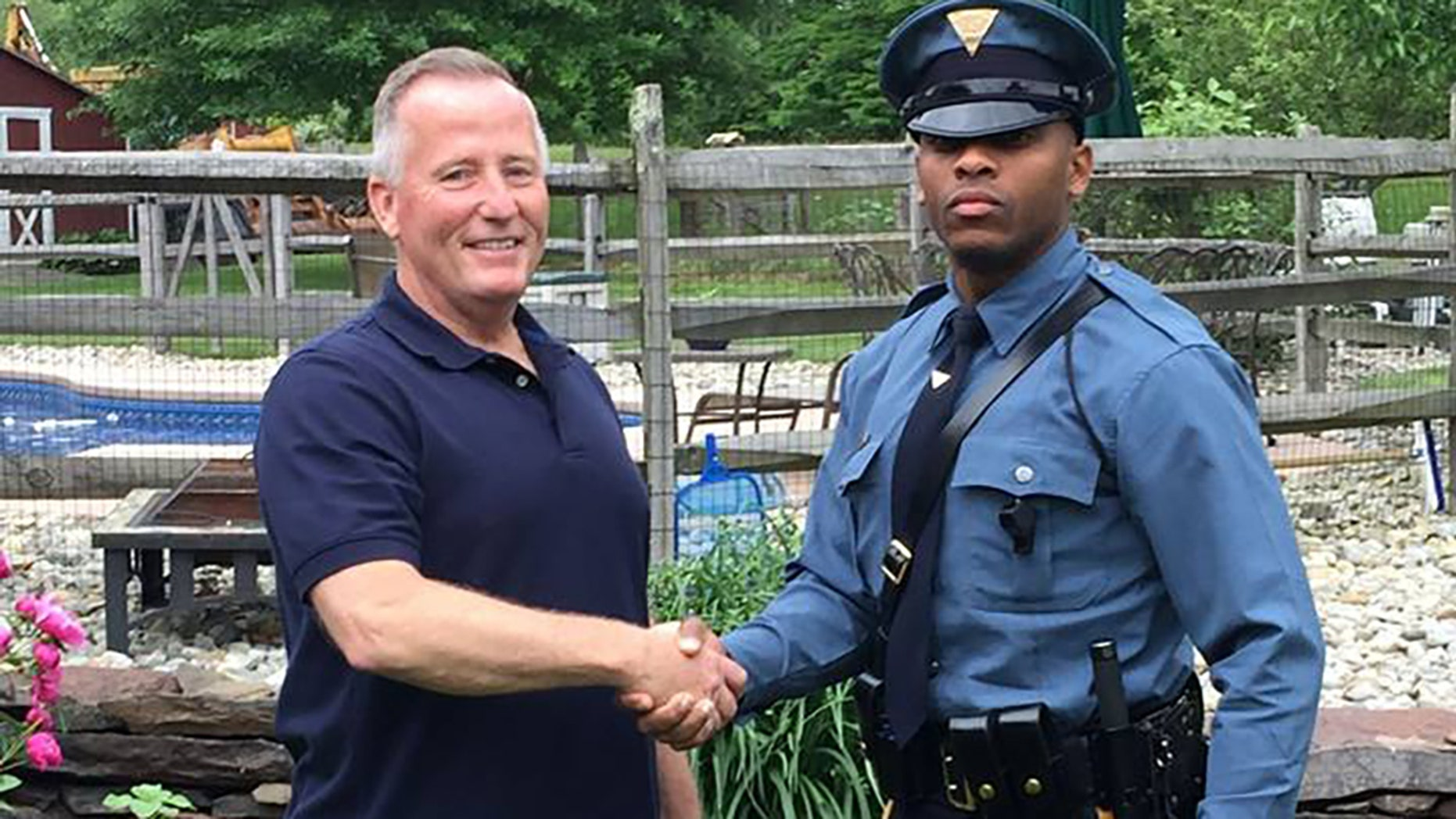 Retired New Jersey police officer Matthew Bailly (left) shaking hands with New Jersey State Trooper Michael Patterson (right) after realizing he helped deliver the trooper 27 years ago.