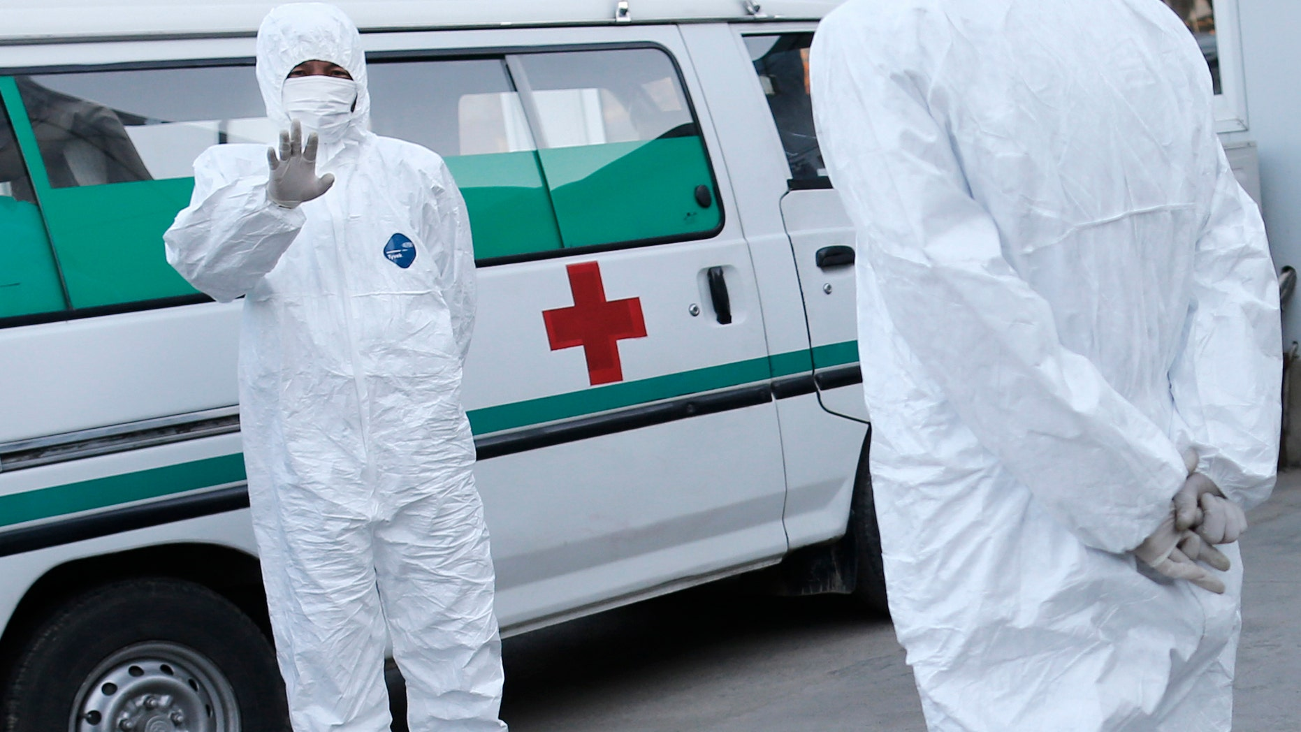 Oct. 27, 2014: Medical personnel in protective suits stand by an ambulance at the Sunan International Airport in Pyongyang, North Korea