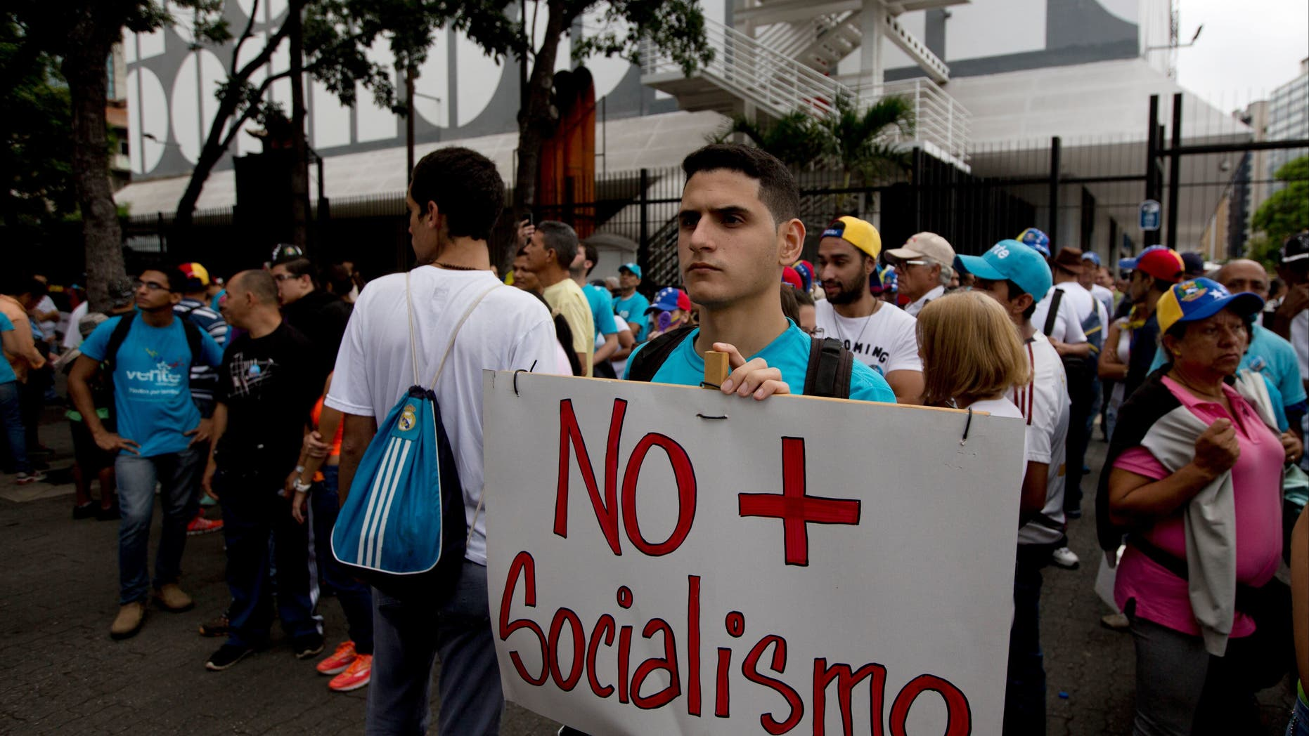 A young man holds poster that reads 'No more Socialism'  in Caracas, Venezuela, Thursday, Sept 1, 2016.