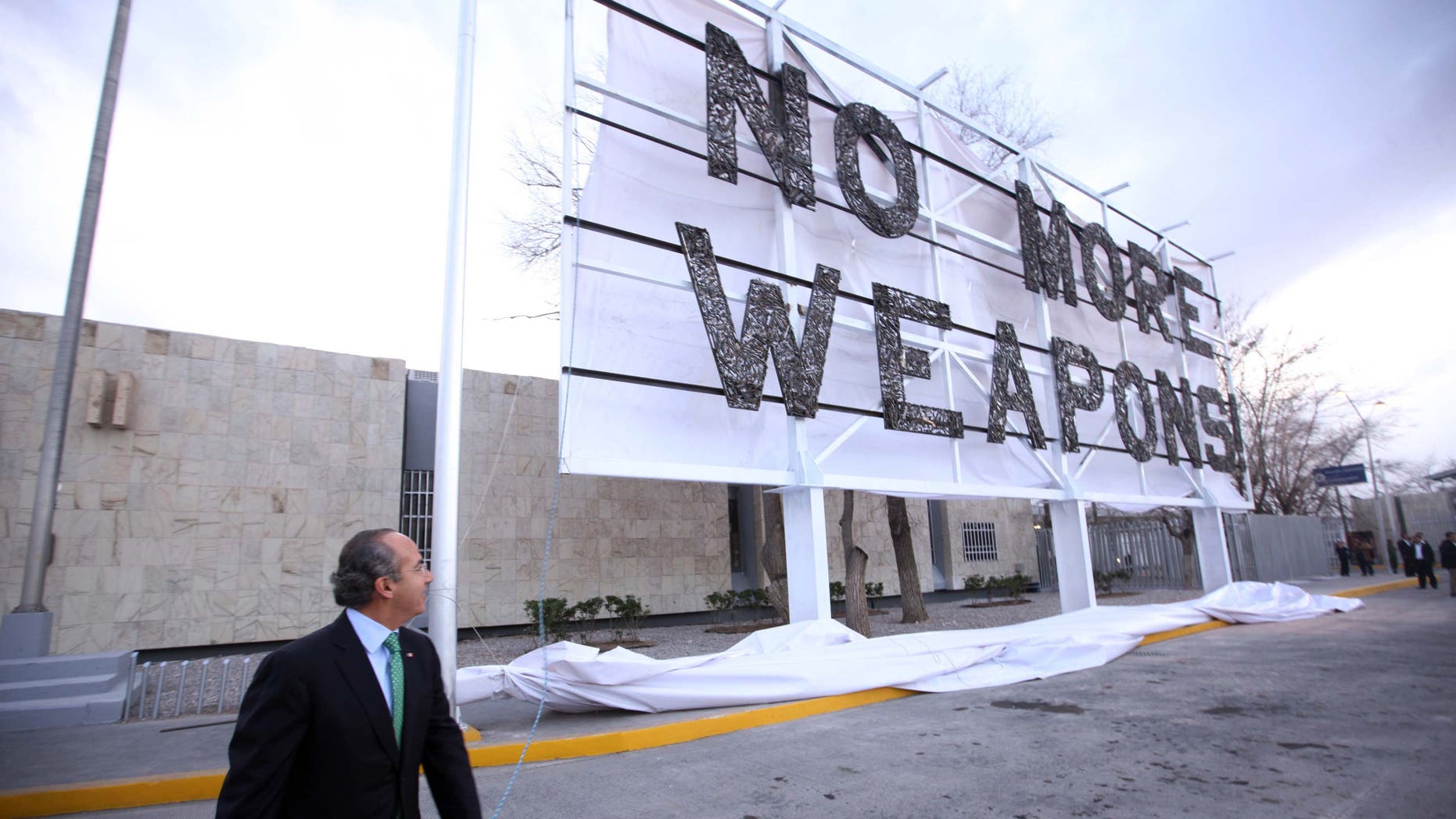 Mexico President Felipe Calderon near the new billboard placed along the U.S.-Mexico border, urging the United States to stop the weapons flow into Mexico.