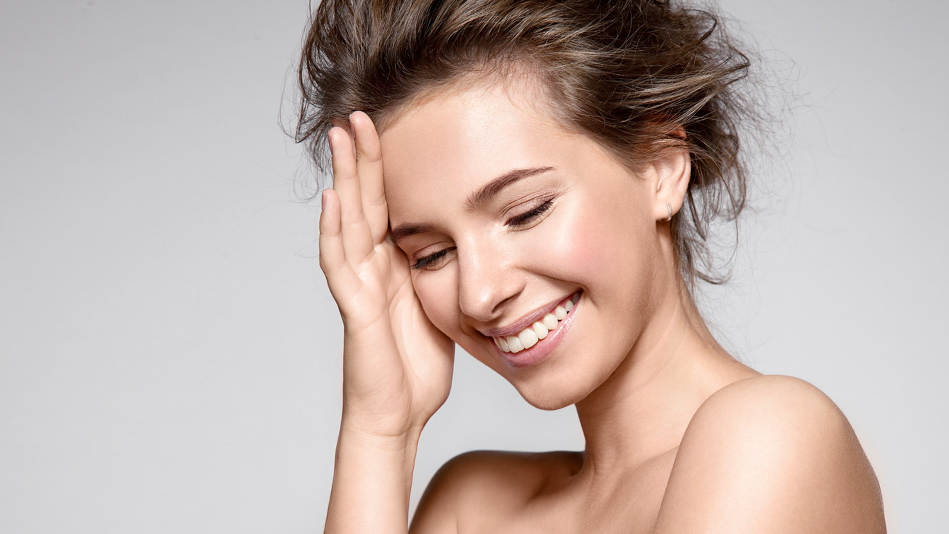 Beautiful smiling woman with natural make-up, clean skin and white teeth on  grey