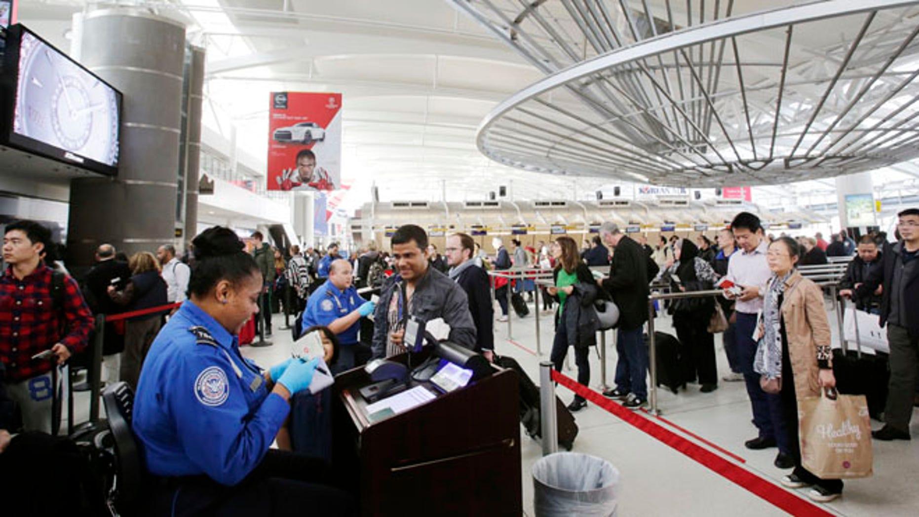 Oct. 30, 2014: A TSA officer, left, checks a passenger's ticket, boarding pass and passport as part of security screening at John F. Kennedy International Airport in New York. (AP)