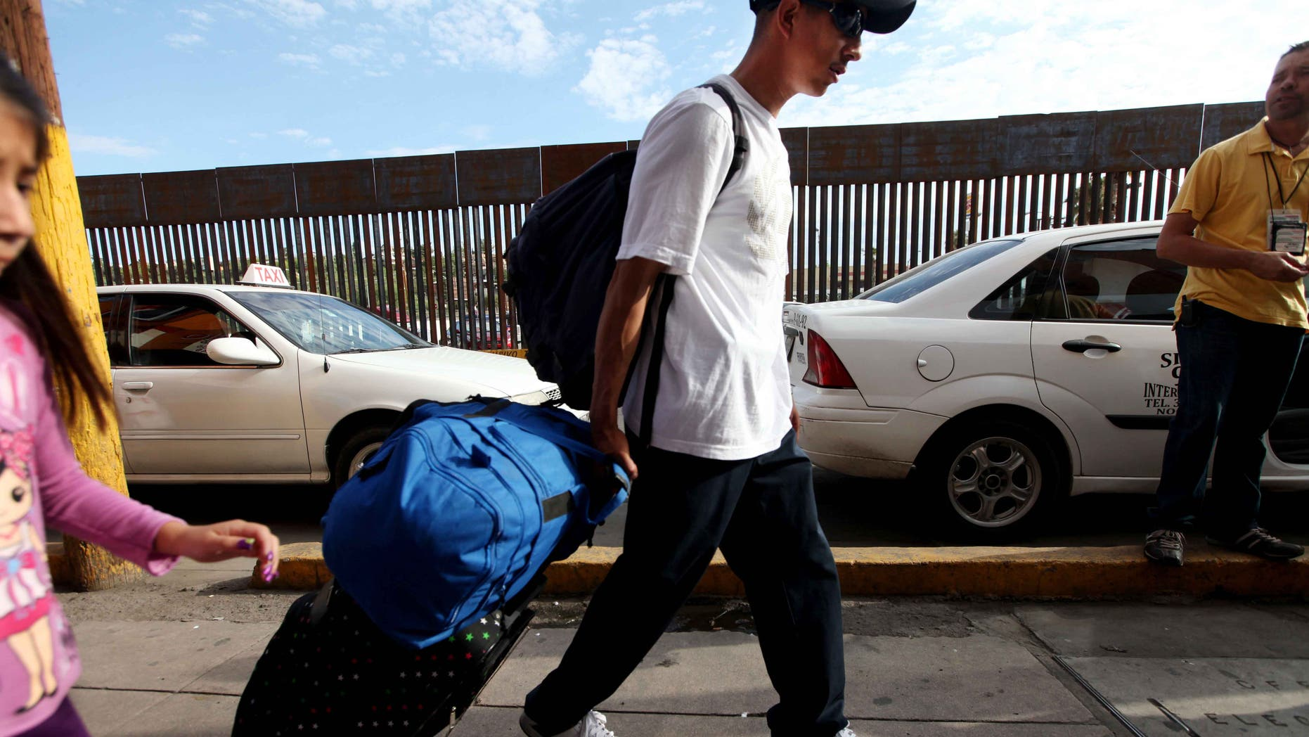 NOGALES, MEXICO - JULY 7:  A mexican national carts his luggage towards the U.S-Mexico border on July 7, 2012 in Nogales, Mexico. The president-elect of Mexico, Enrique Peña Nieto, stated that he wants to expand his country's drug-war partnership with the United States but that he would not support the presence of armed American agents in Mexico.  (Photo by Sandy Huffaker/Getty Images)