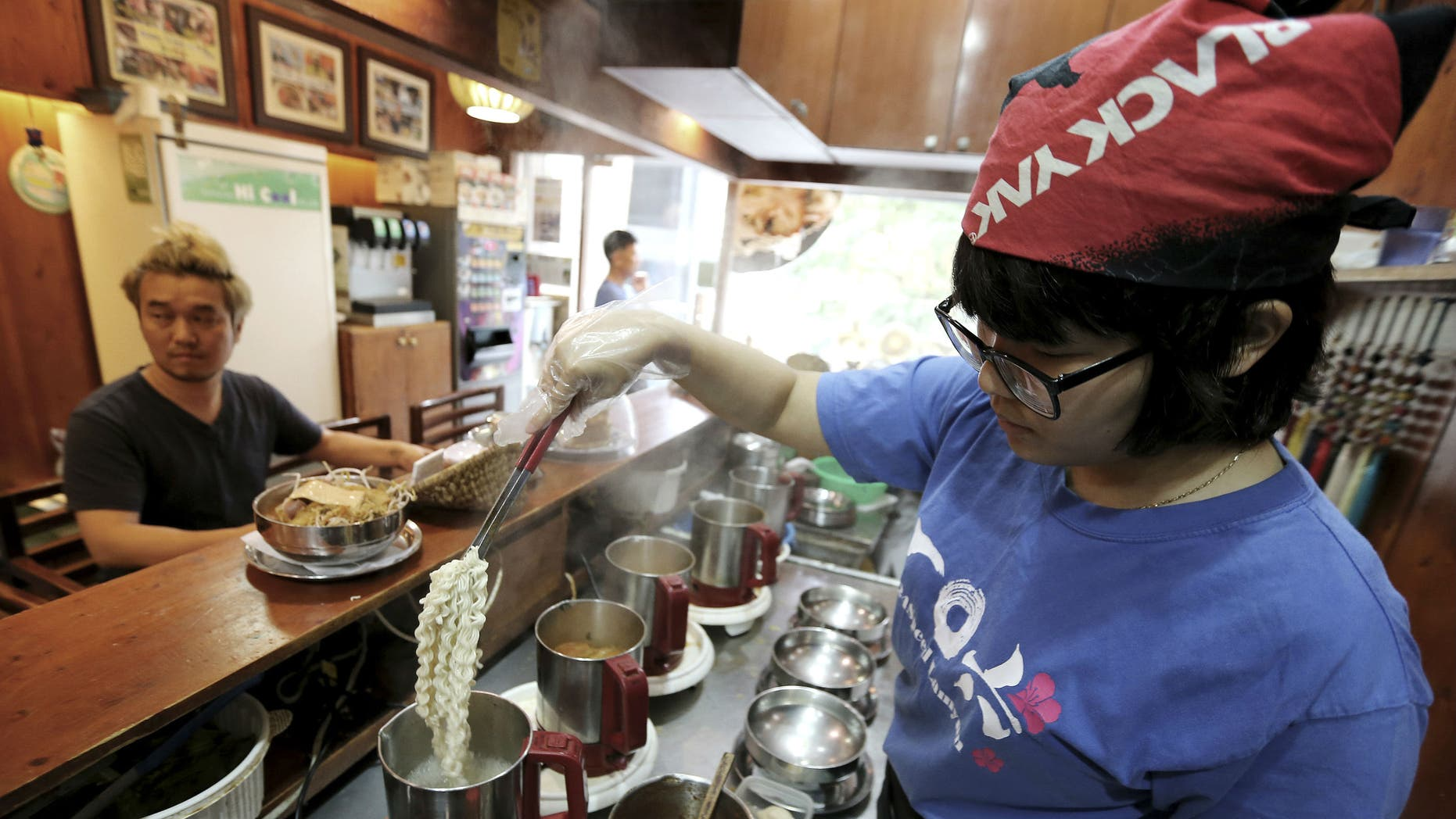 """In this Aug. 19. 2014 photo, a cook prepares """"ramyeon"""" instant noodles for Han Seung-youn, left, during an interview at a ramyeon restaurant in Seoul, South Korea. (AP Photo/Ahn Young-joon )"""
