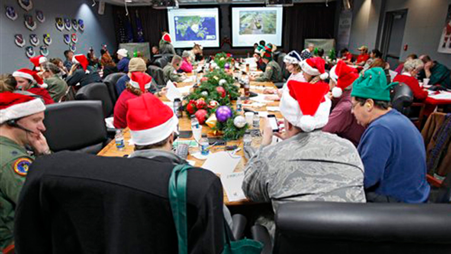 FILE - In this Dec. 24, 2010 file photo, volunteers take phone calls and answer emails at the Santa Tracking Operations Center at Peterson Air Force Base near Colorado Springs, Colo. Santa is already piling up monster numbers on social networking sites this season, so the volunteer Santa-trackers at NORAD are bracing for tens of thousands of calls and emails when their operations center goes live on Christmas Eve. (AP Photo/Ed Andrieski, File)