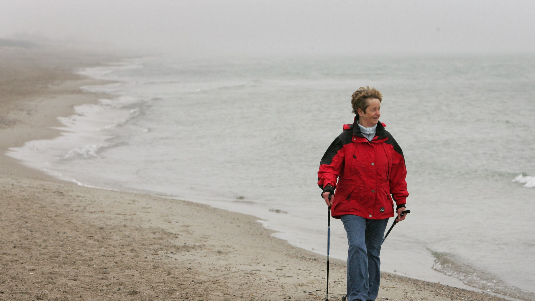 An elderly woman practices Nordic walking for rehabilitation exercise on the beach outside at a clinic in Damp on Germany's Baltic sea coast April 13, 2006.    REUTERS/Christian Charisius - RTR1CQ1G
