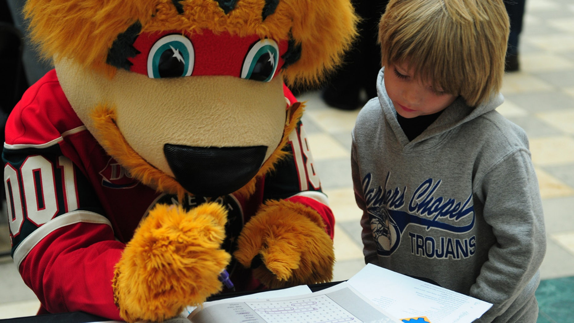 Nordy, the Minnesota Wild mascot, helps a youngster work on a word find during a post office event in 2013.