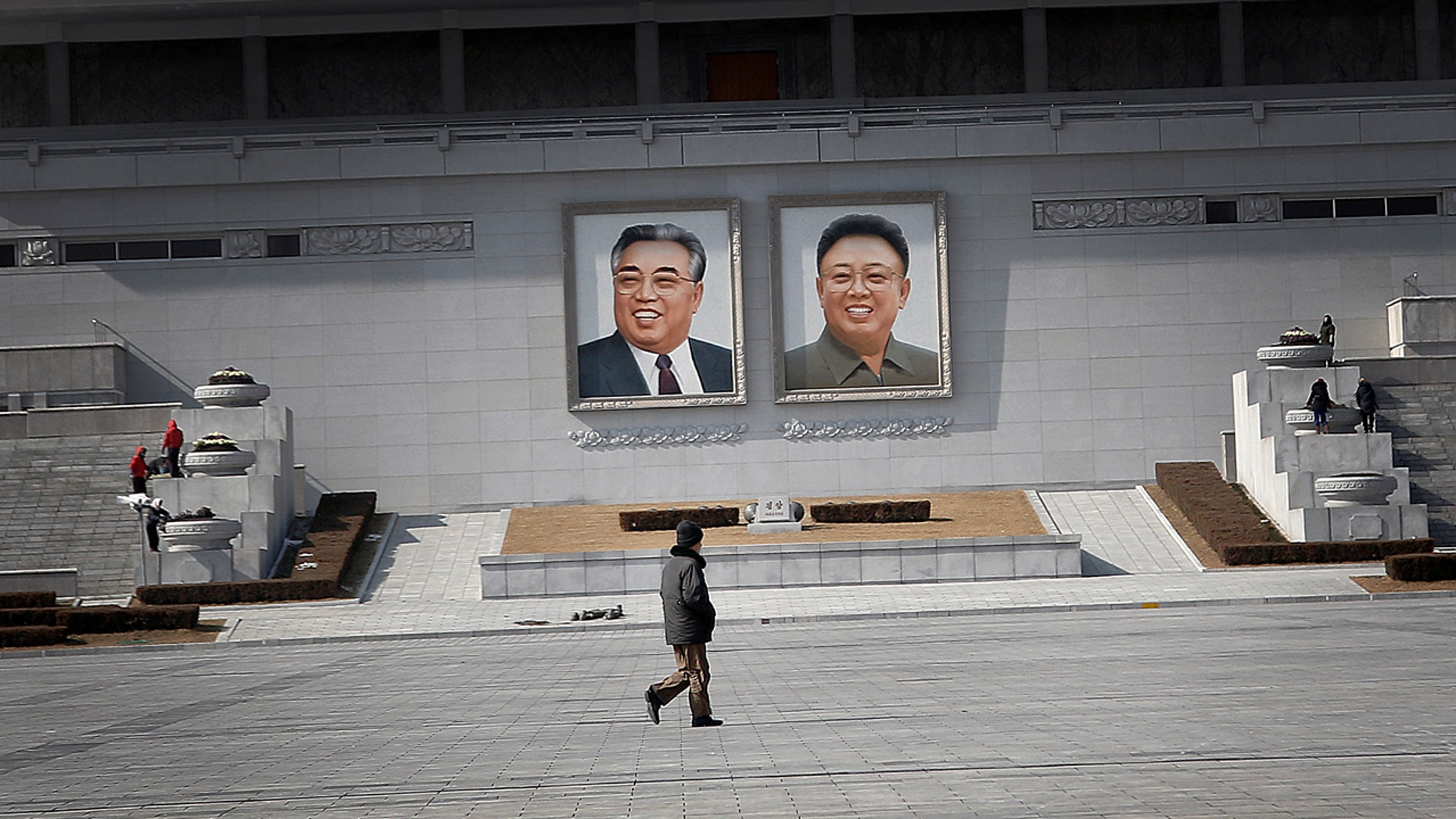 Feb. 14, 2016: A man walks past portraits of the late North Korean leaders Kim Il Sung and Kim Jong Il at Kim Il Sung Square in Pyongyang, North Korea (AP/Wong Maye-E)