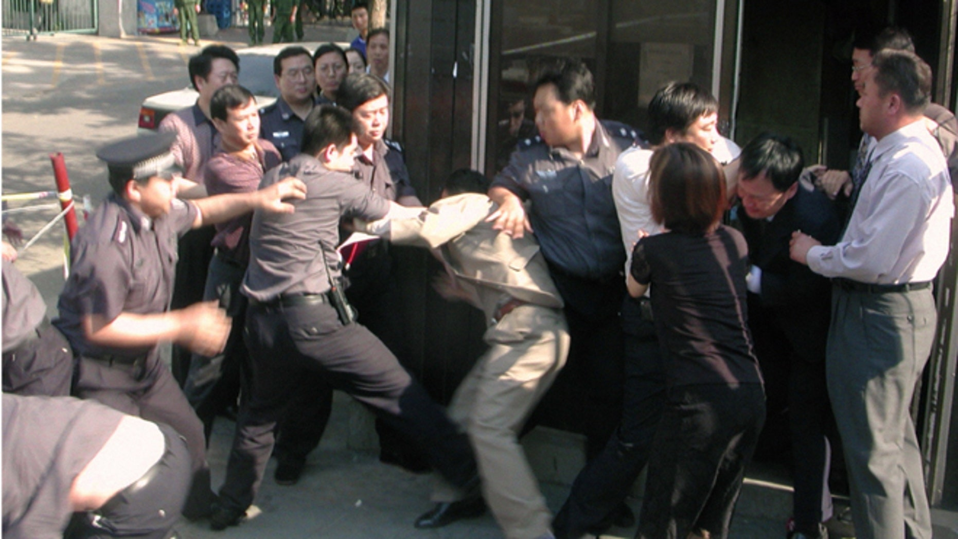 In this June 13, 2002 photo, Chinese security officers and officials at South Korean Embassy in Beijing scuffle in front of a police guard box next to the embassy's main gate as the security officers attempted to drag away a North Korean asylum seeker. Two North Koreans entered the embassy on June 13, 2002 amid a spate of asylum bids by North Koreans, but Chinese guards dragged an asylum-seeker from the visa office after punching and kicking diplomats who tried to block them.