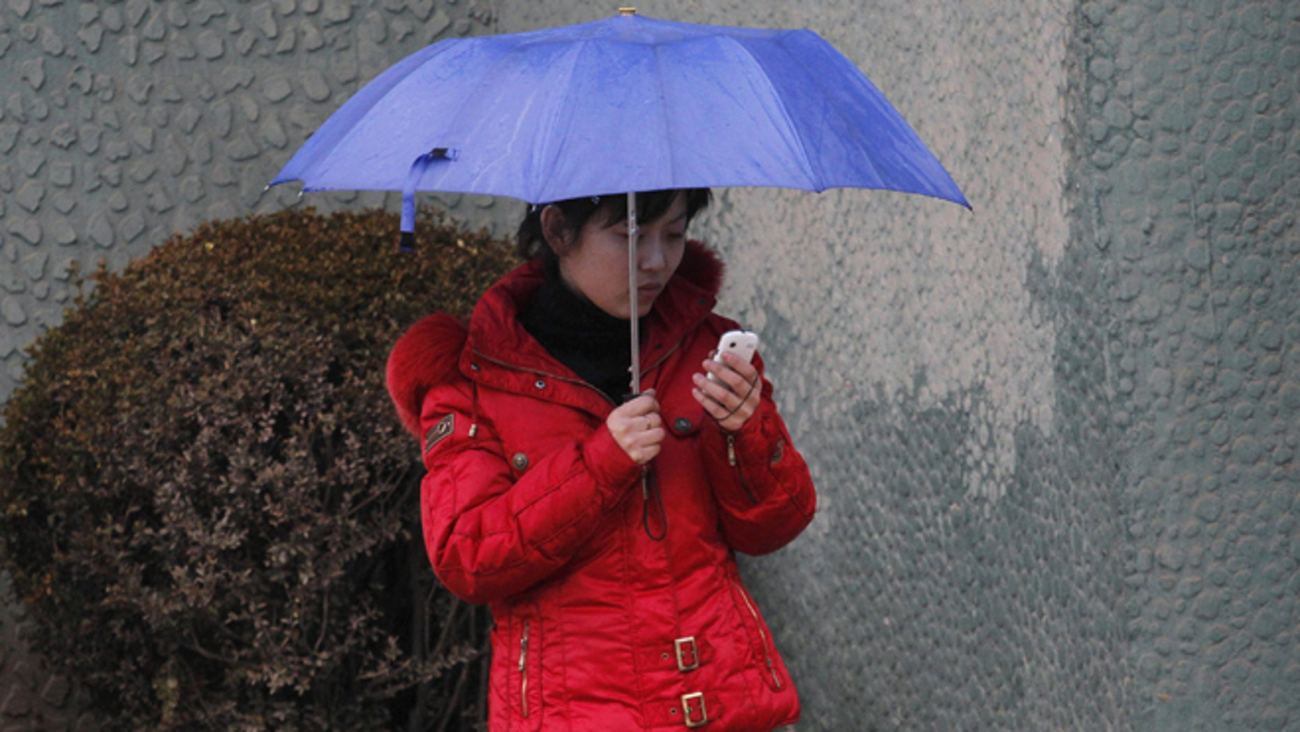 March 16, 2012: In this file photo, a North Korean woman uses a cellphone on a sidewalk in Pyongyang, North Korea. North Korea is loosening its restrictions on foreign cellphones and is allowing visitors to bring their own phones into the country.