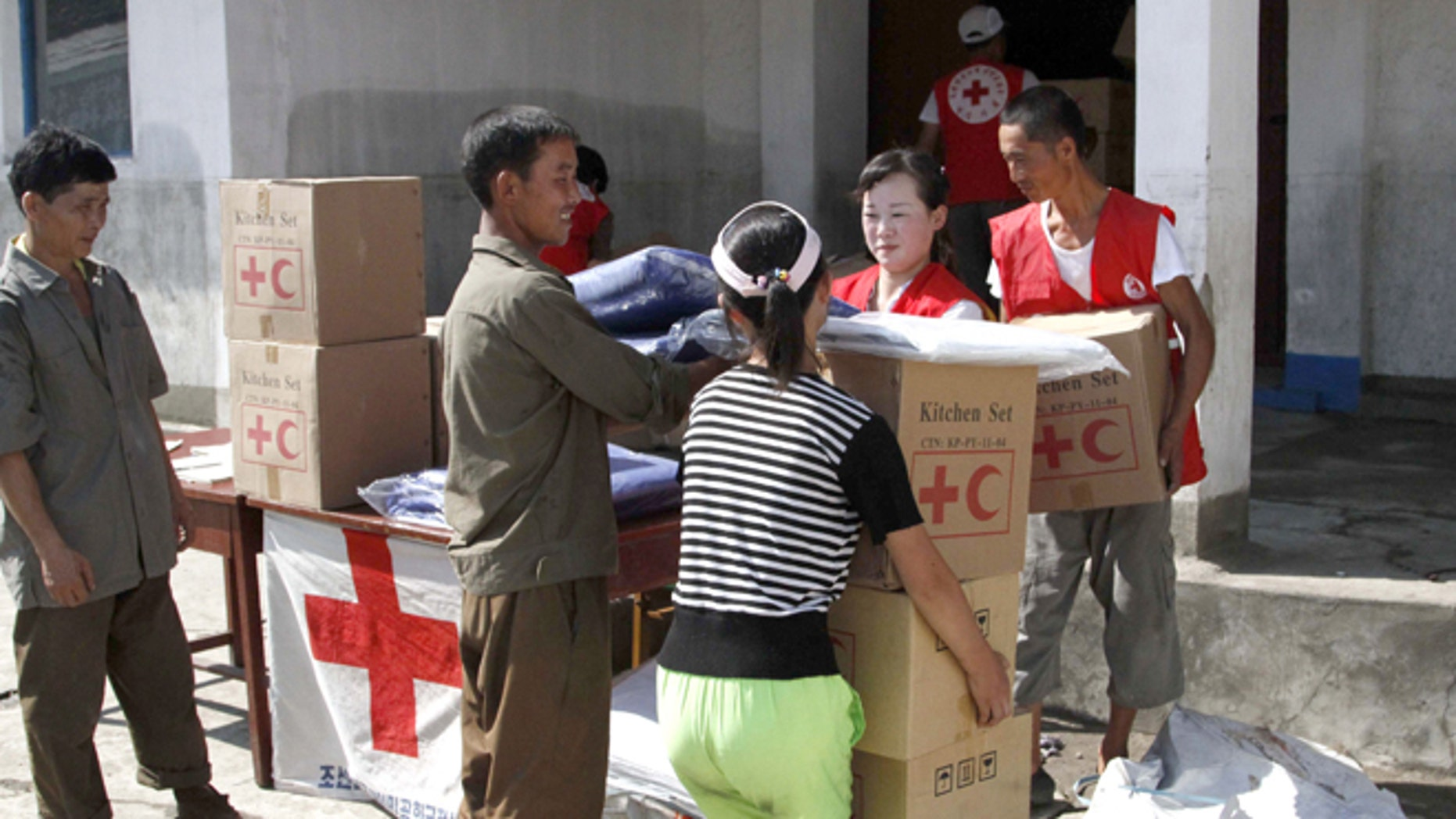 Aug. 4, 2012: Residents collect emergency goods, including kitchen sets and blankets, distributed by North Korean Red Cross officials in the flood-stricken city of Anju in South Phyongan Province, North Korea.