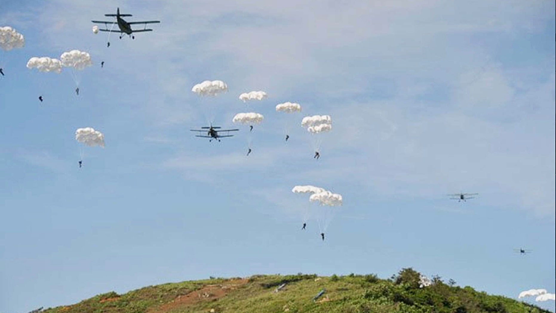 North Korea paratroopers jump out of two Antonov An-2 transport aircrafts.
