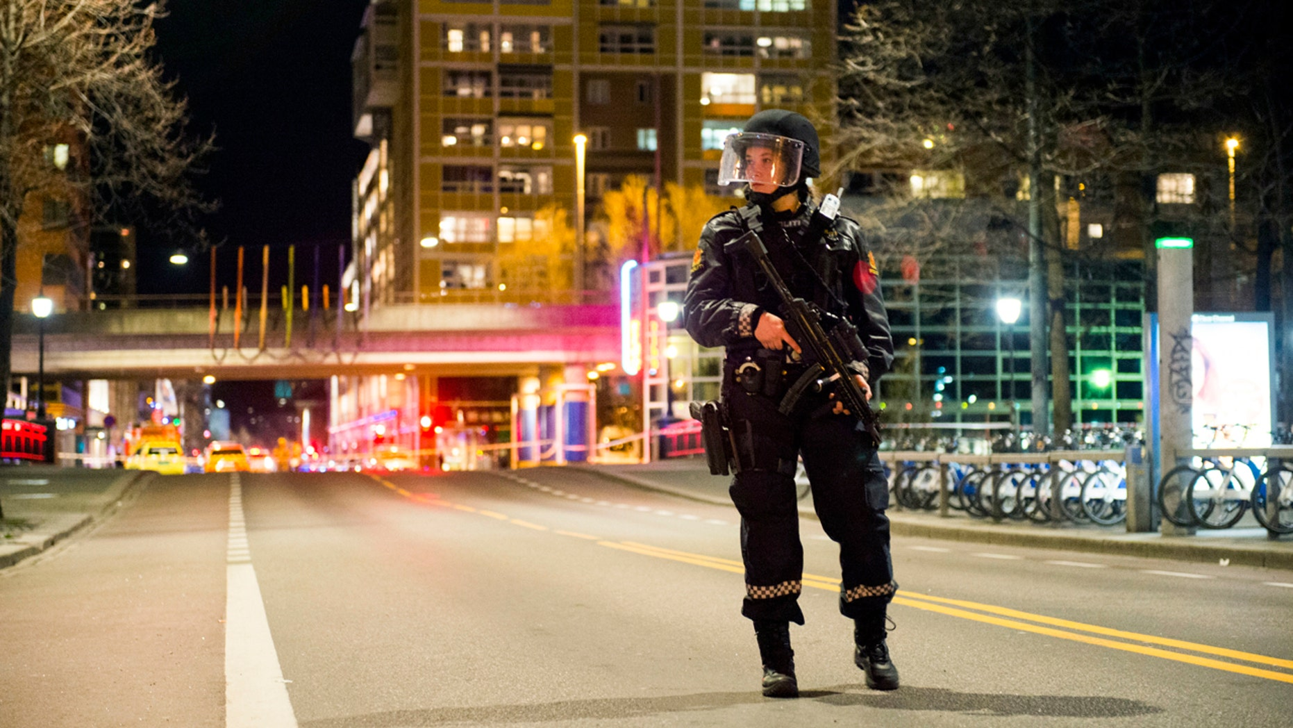"""An officer stands guard as police cordon off a large area around a subway station on a busy commercial street Saturday night, April 8, 2017, after finding what they described as a """"bomb-like"""" device, in Oslo, Norway."""