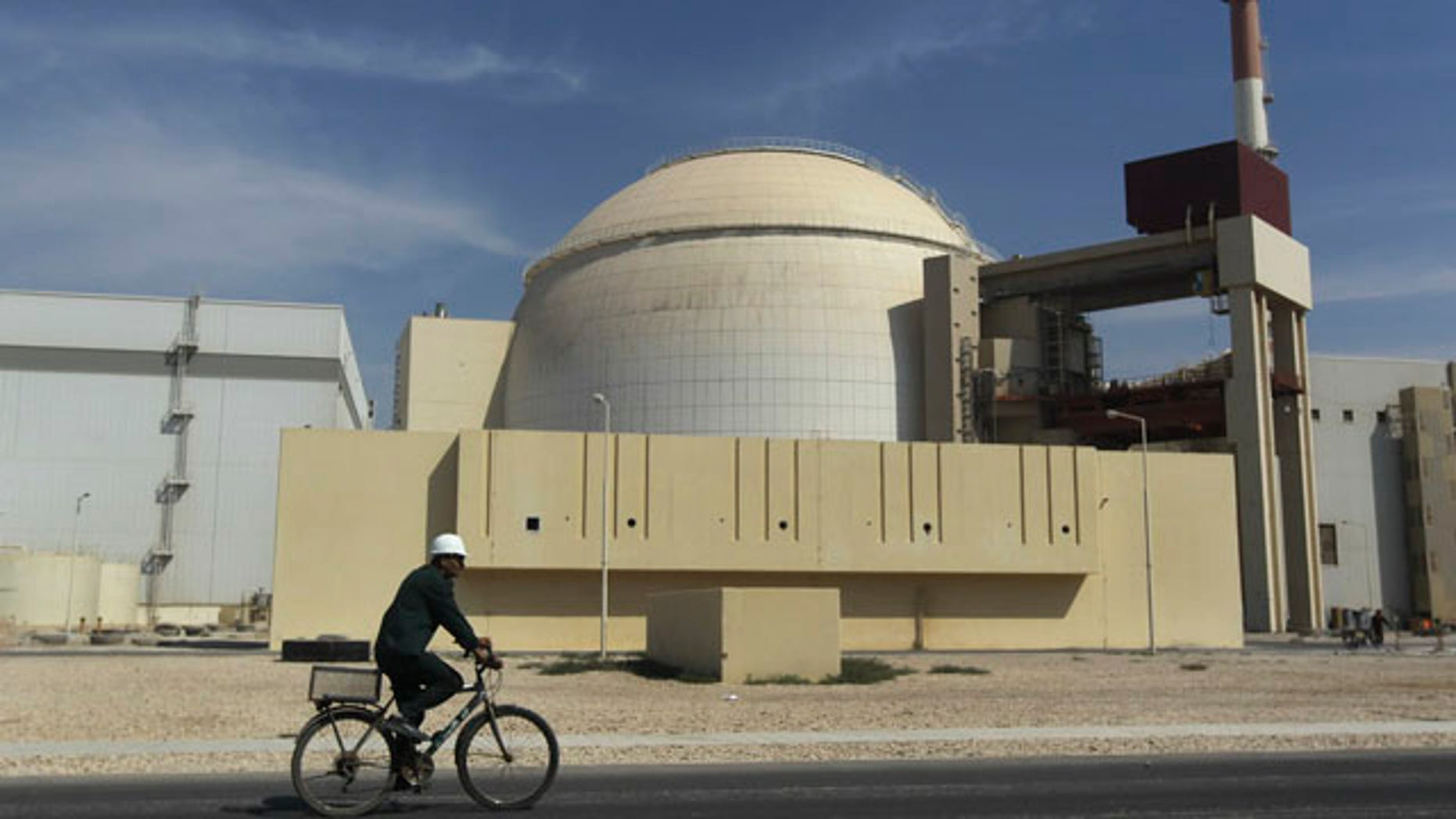 Oct. 26, 2010: A worker rides a bike in front of the reactor building of the Bushehr nuclear power plant, just outside the southern city of Bushehr, Iran.