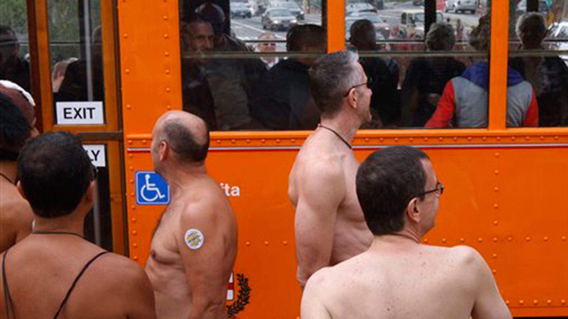 A Muni F-Market line streetcar rolls past nudists at Castro and 17th streets, Saturday, Sept. 24, 2011, in San Francisco. Originally organized to celebrate the Folsom Street Fair, the nude-in gained popularity after Supervisor Scott Wiener's proposal to force nudists to sit on handkerchiefs or towels in public.