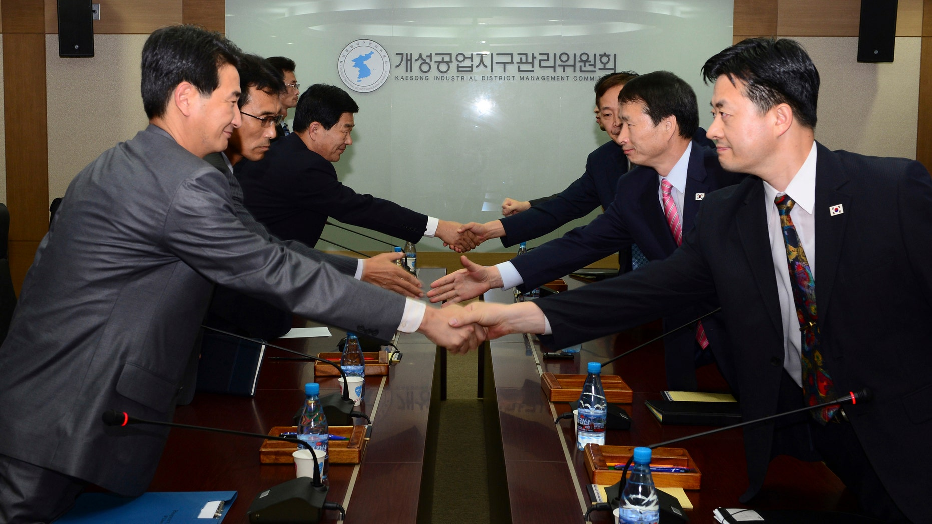 In this photo released by Unification Ministry, South Korean delegates, right, shake hands with their North Korean counterparts at the start of a meeting at Kaesong Industrial District Management Committee in Kaesong, North Korea, Wednesday, Sept. 11, 2013.