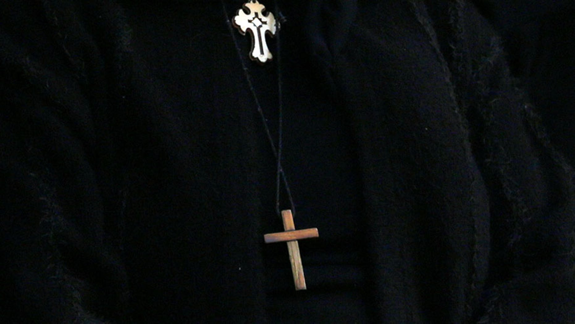 A cross is seen on the clothes of Egyptian Christians during the funeral of victims killed in the bombing of Cairo's Coptic cathedral, at the Mokattam Cemetery in Cairo, Egypt December 12, 2016. REUTERS/Amr Abdallah Dalsh - RTX2UP8B