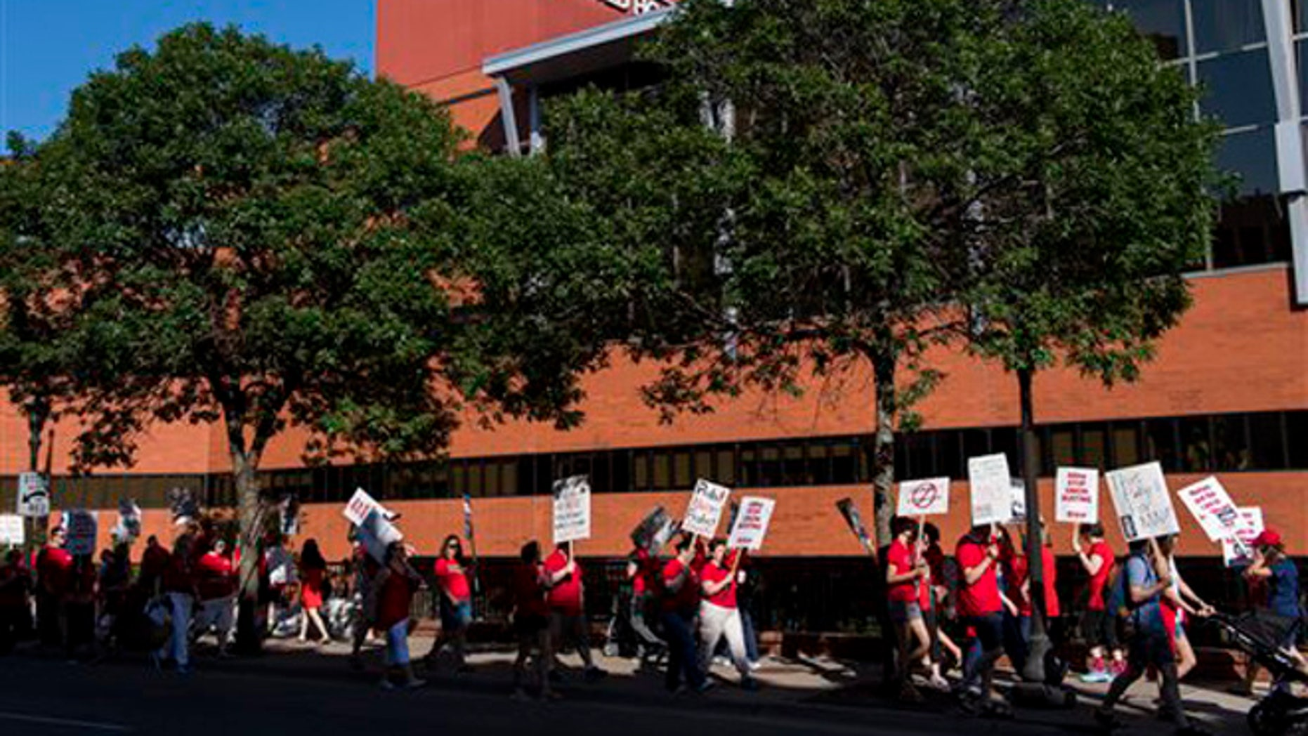 Picketers walk in front of United Hospital in St. Paul, Minn., Sunday, June 19. 2016.