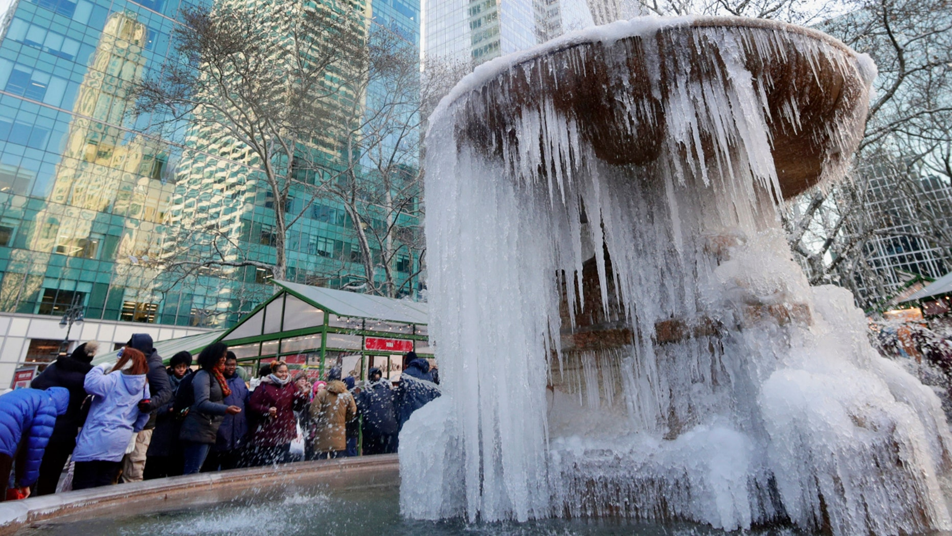 People pose for photos near a frozen water fountain in New York City's Bryant Park, Dec. 28, 2017.