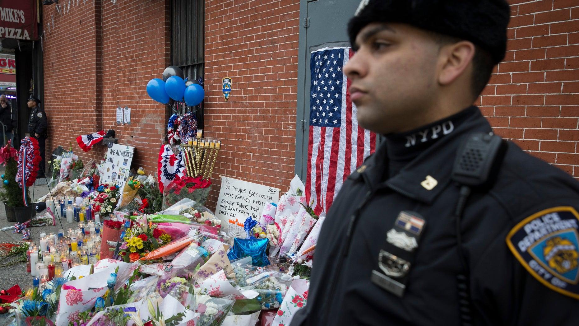Dec. 22, 2014: A New York Police Department officer stands guard beside a makeshift memorial.
