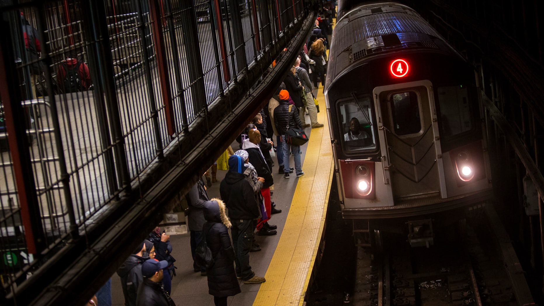 Commuters wait to ride New York City Subway in New York, December 12, 2013.