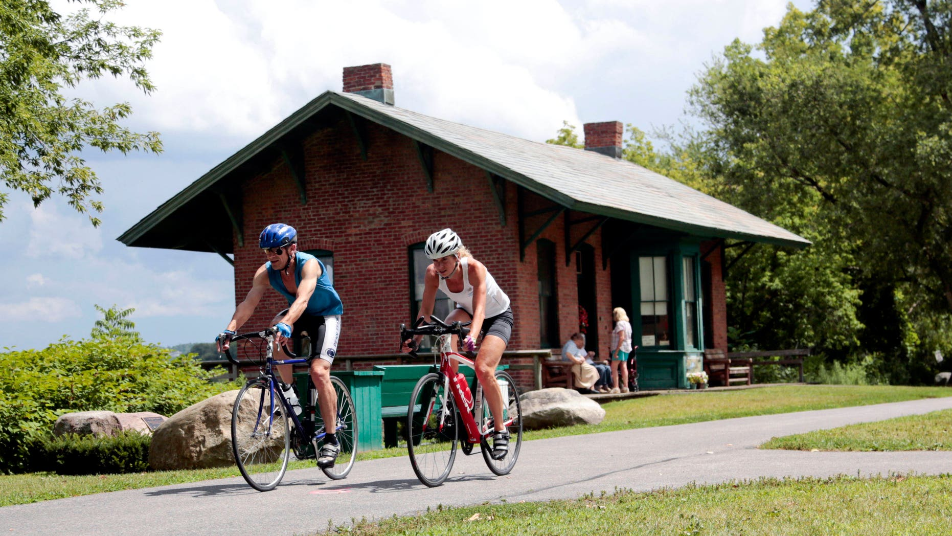 FILE- In this Tuesday, Aug. 4, 2015 file photo, cyclists pass the Niskayuna Train Station as they bike on the Canalway Trail in Niskayuna, N.Y. Gov. Andrew Cuomo proposed a a 750-mile paved biking and hiking Empire State Trail, of which the Canalway Trail would be part of. (AP Photo/Mike Groll, File)